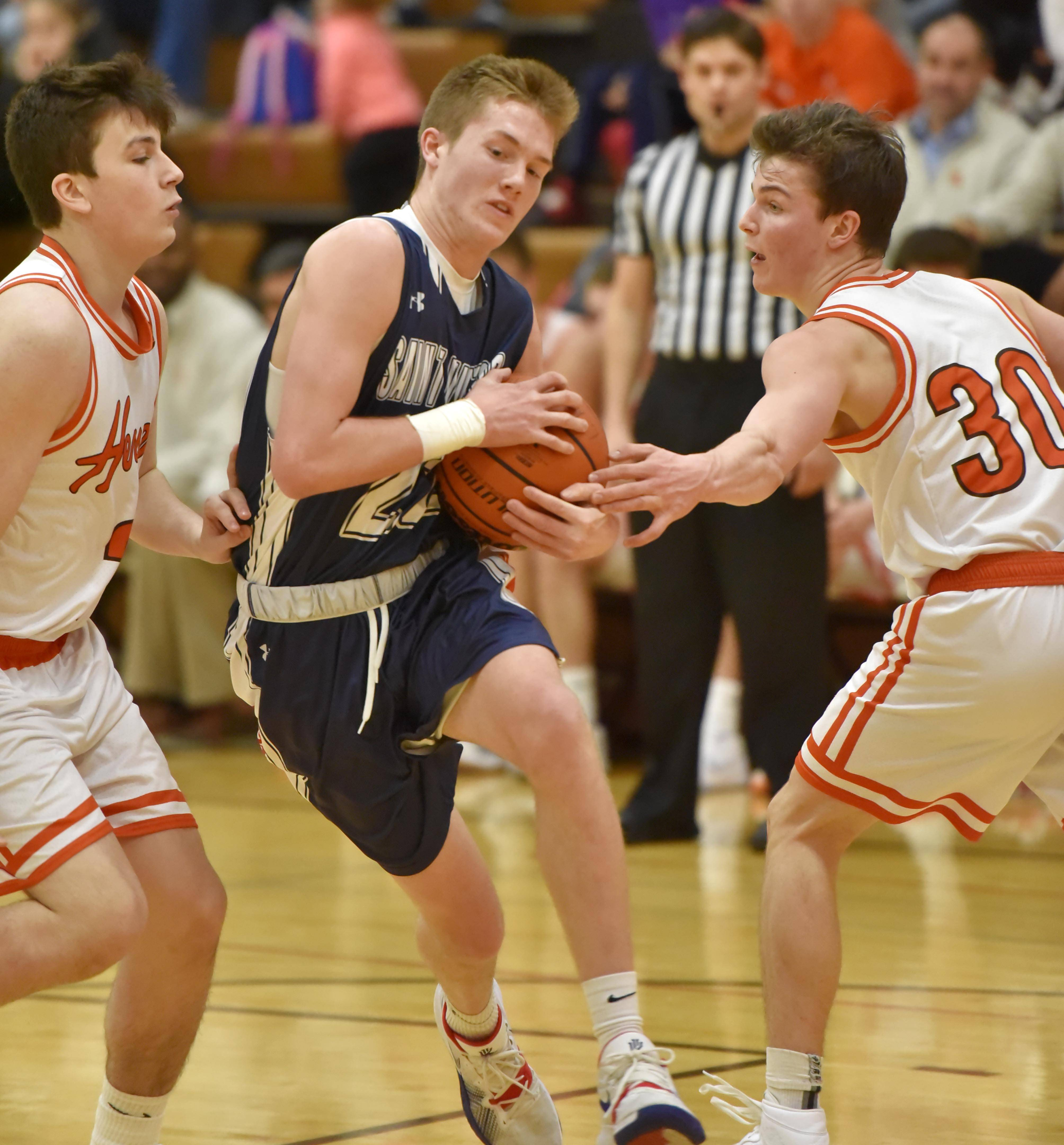 St. Viator's Kevin Murphy drives between Hersey's Brent Wolff and Jason Schmidt, right, Saturday in a boys basketball game in Arlington Heights.