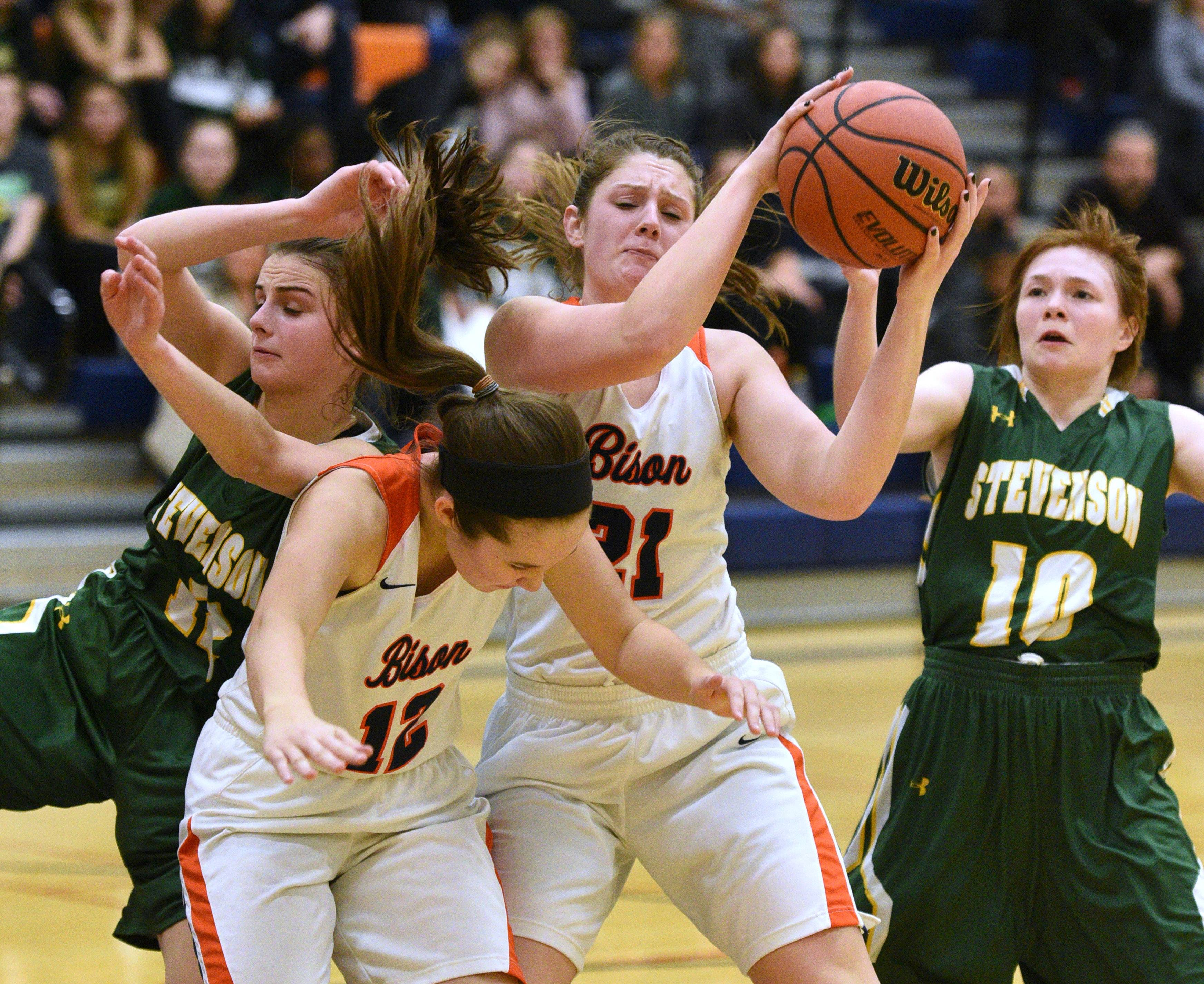 Stevenson's Kristin Hill, left, and Nicole Ware, right, battle for the rebound with Buffalo Grove's Hannah Young (12) and Sydney Fortman (21) during Monday's girls basketball game in Buffalo Grove.