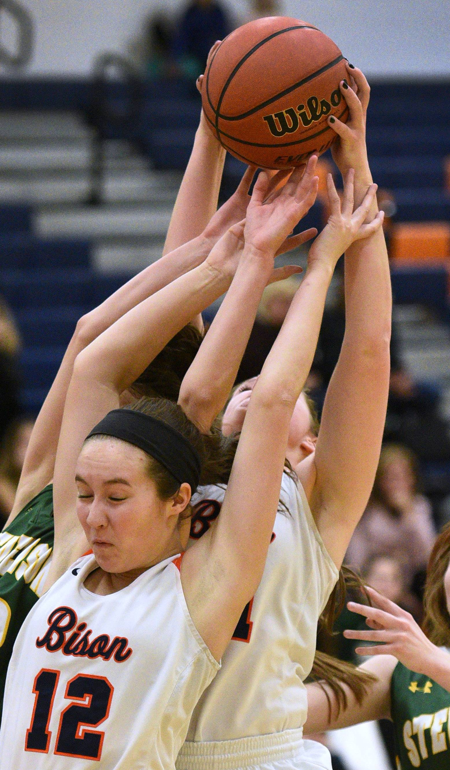Buffalo Grove's Hannah Young (12) is in the thick of a rebound battle during Monday's girls basketball game against Stevenson in Buffalo Grove.