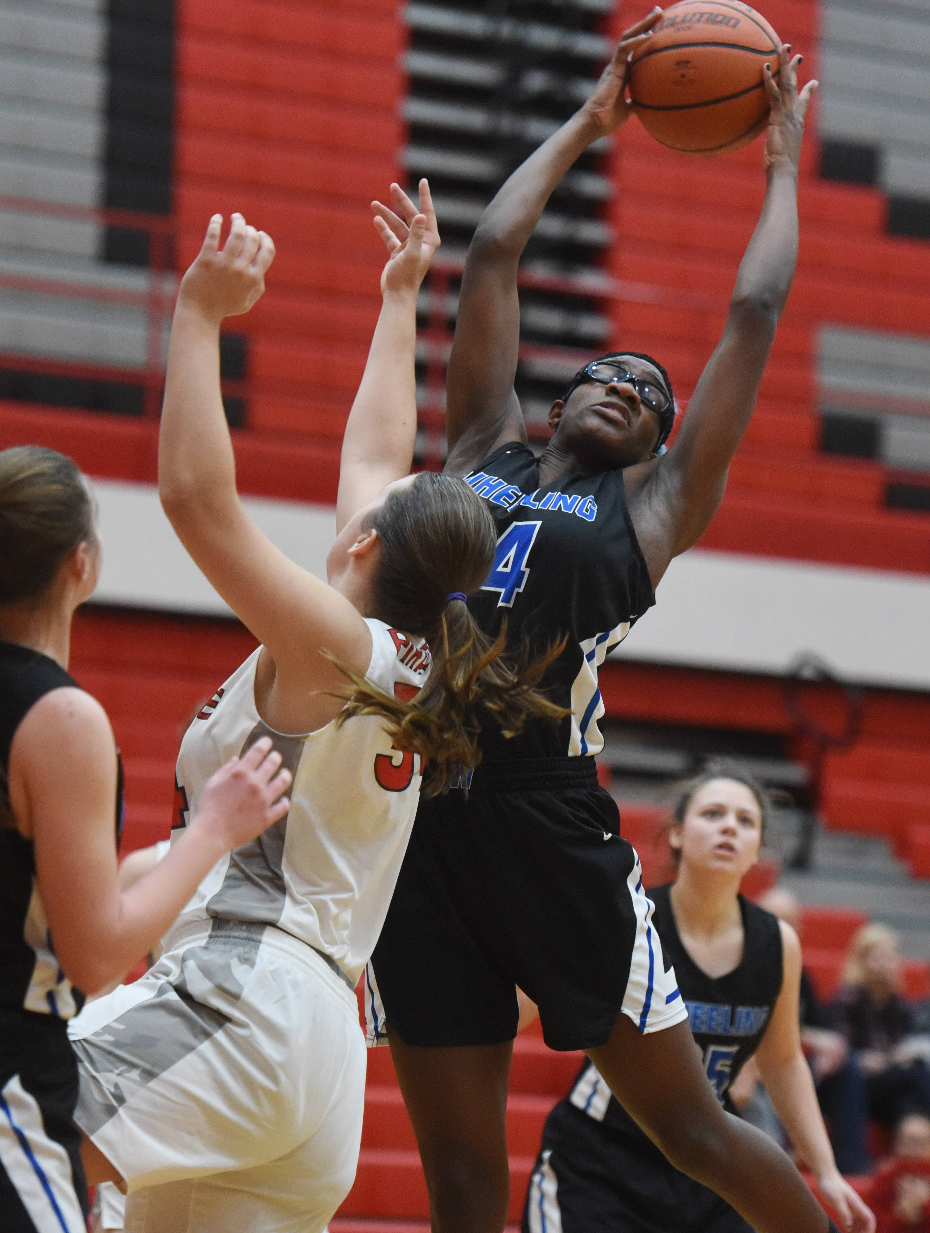 Wheeling's Nosa Igiehon, right, grabs a rebound in front of Palatine's Kayla Miotk during Tuesday's game at Palatine.