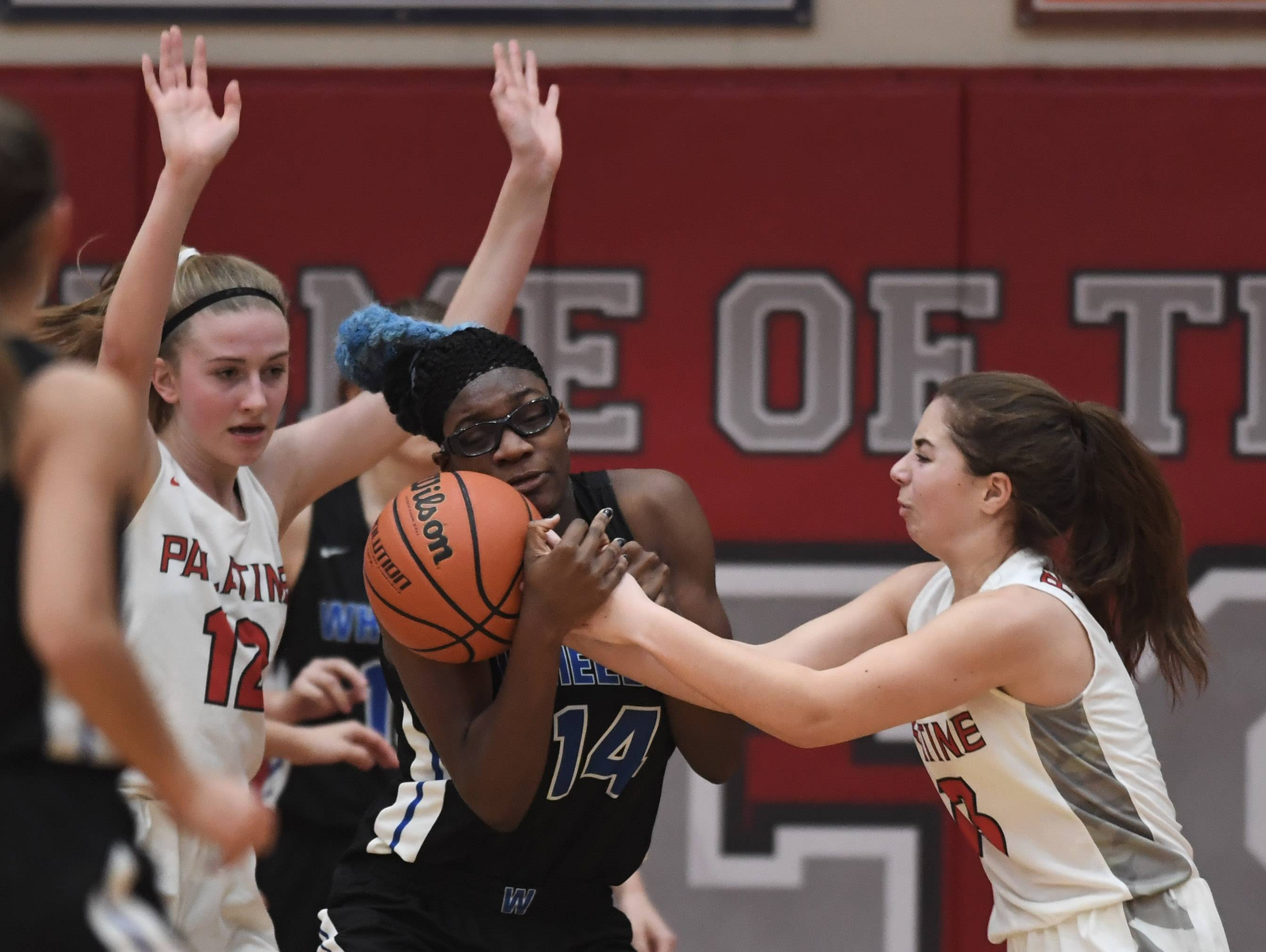 Wheeling's Nosa Igiehon tries to control the ball as Palatine's Julianna Mandarino, right, plays tight defense during Tuesday's game at Palatine.