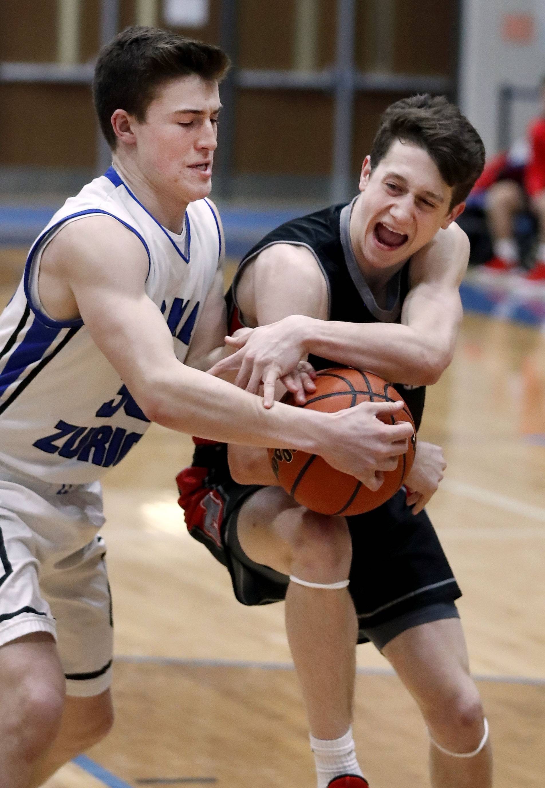 Mundelein's Conor Enright, right, drives on Lake Zurich's William Tucker during their game Tuesday night in Lake Zurich,