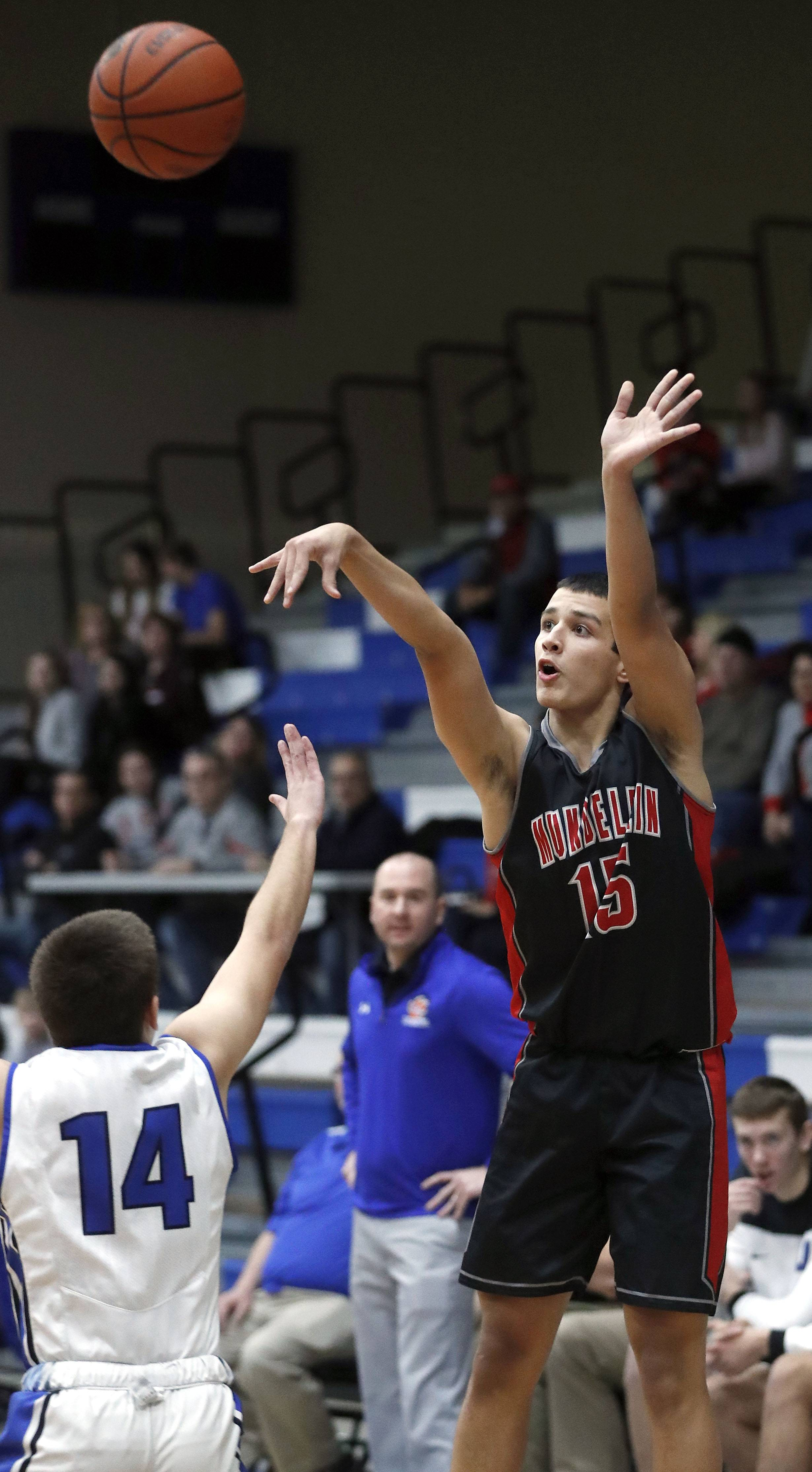 Mundelein's Andrew Gonzalez, right, shoots over Lake Zurich's Austin LePage during their game Tuesday night in Lake Zurich,