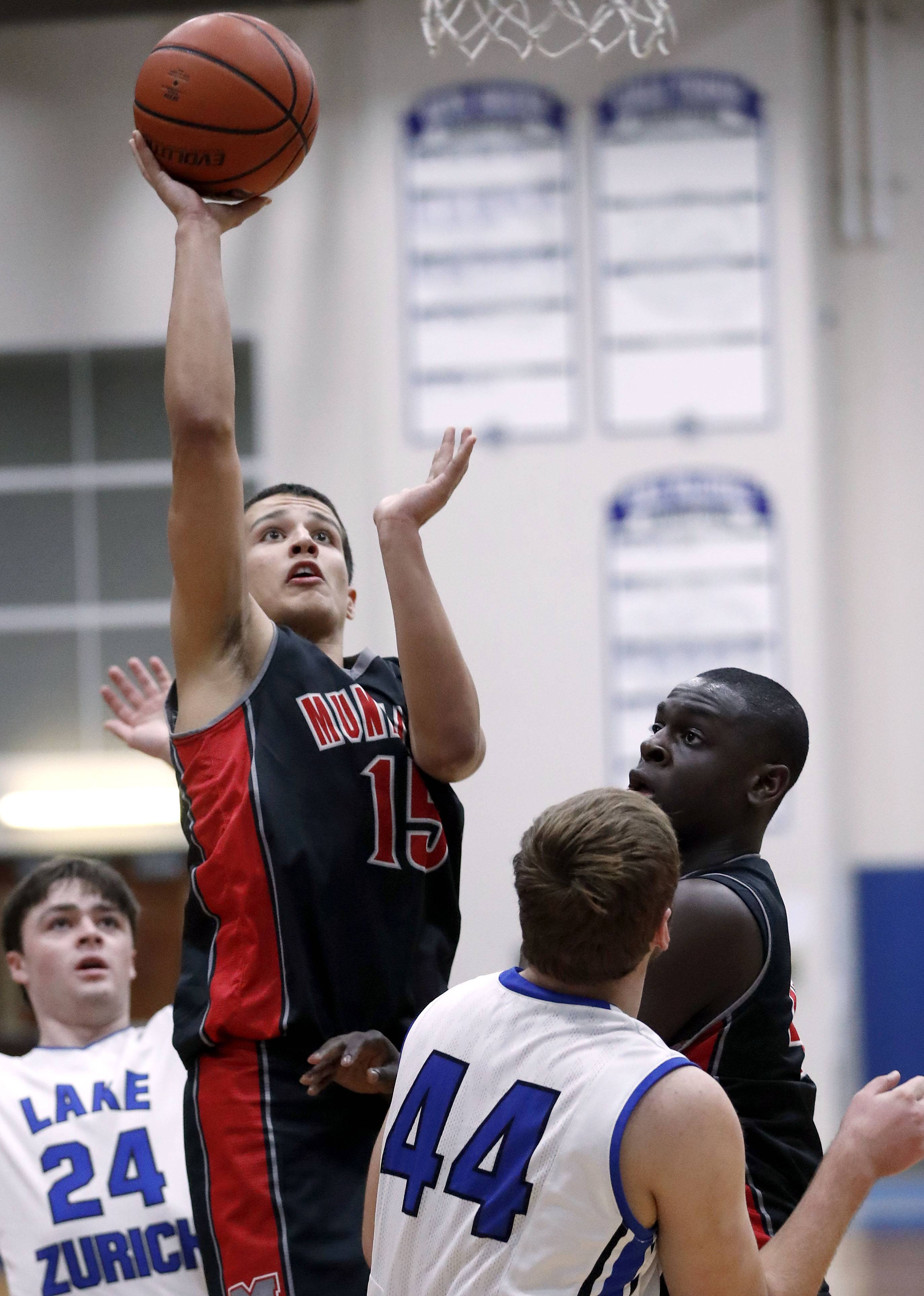 Mundelein's Andrew Gonzalez (15) shoots over Lake Zurich's Nick Marcinkiewicz during their game Tuesday night in Lake Zurich,