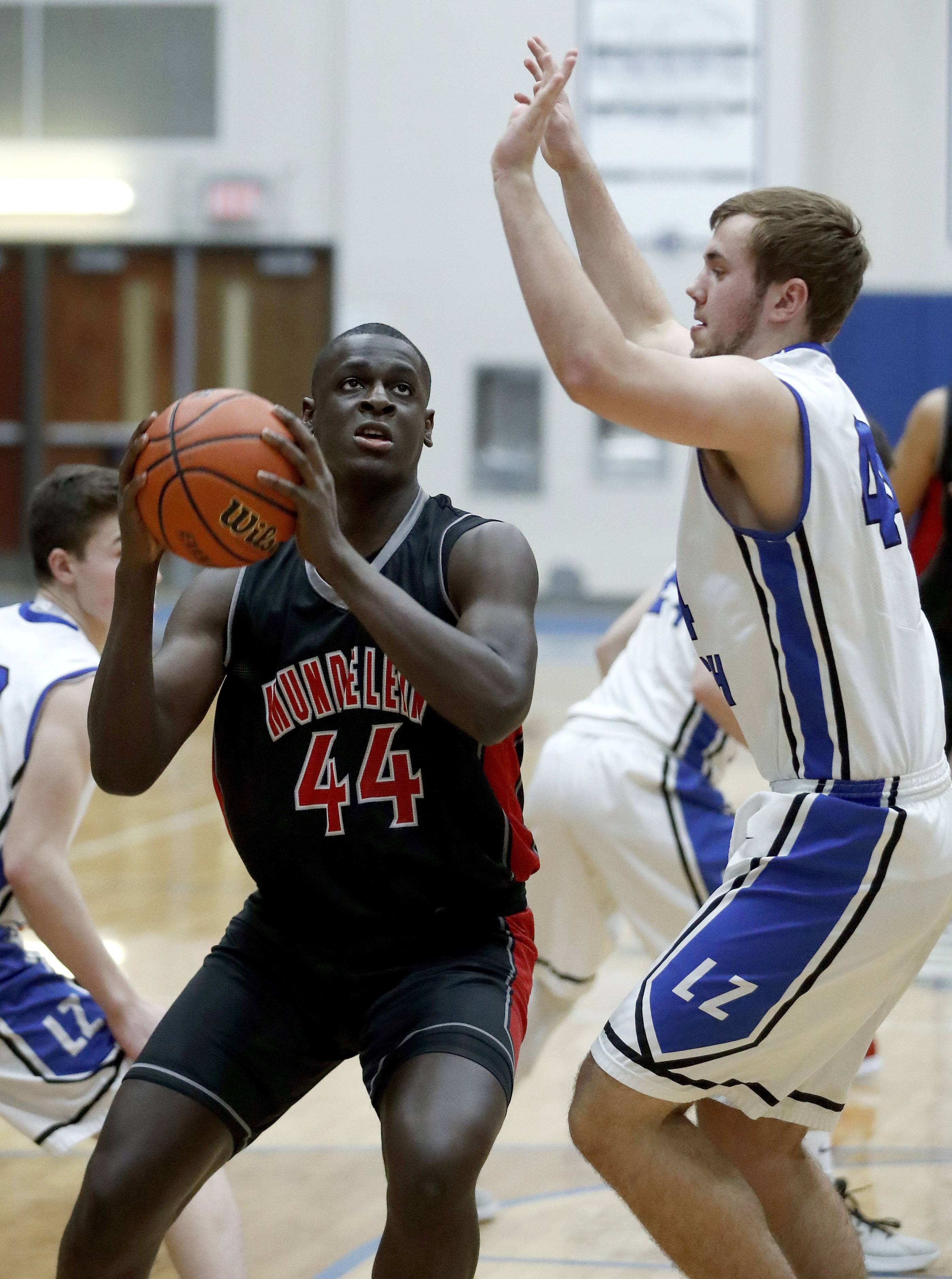Mundelein's Scottie Ebube, left, drives on Lake Zurich's Nick Marcinkiewicz during their game Tuesday night in Lake Zurich,