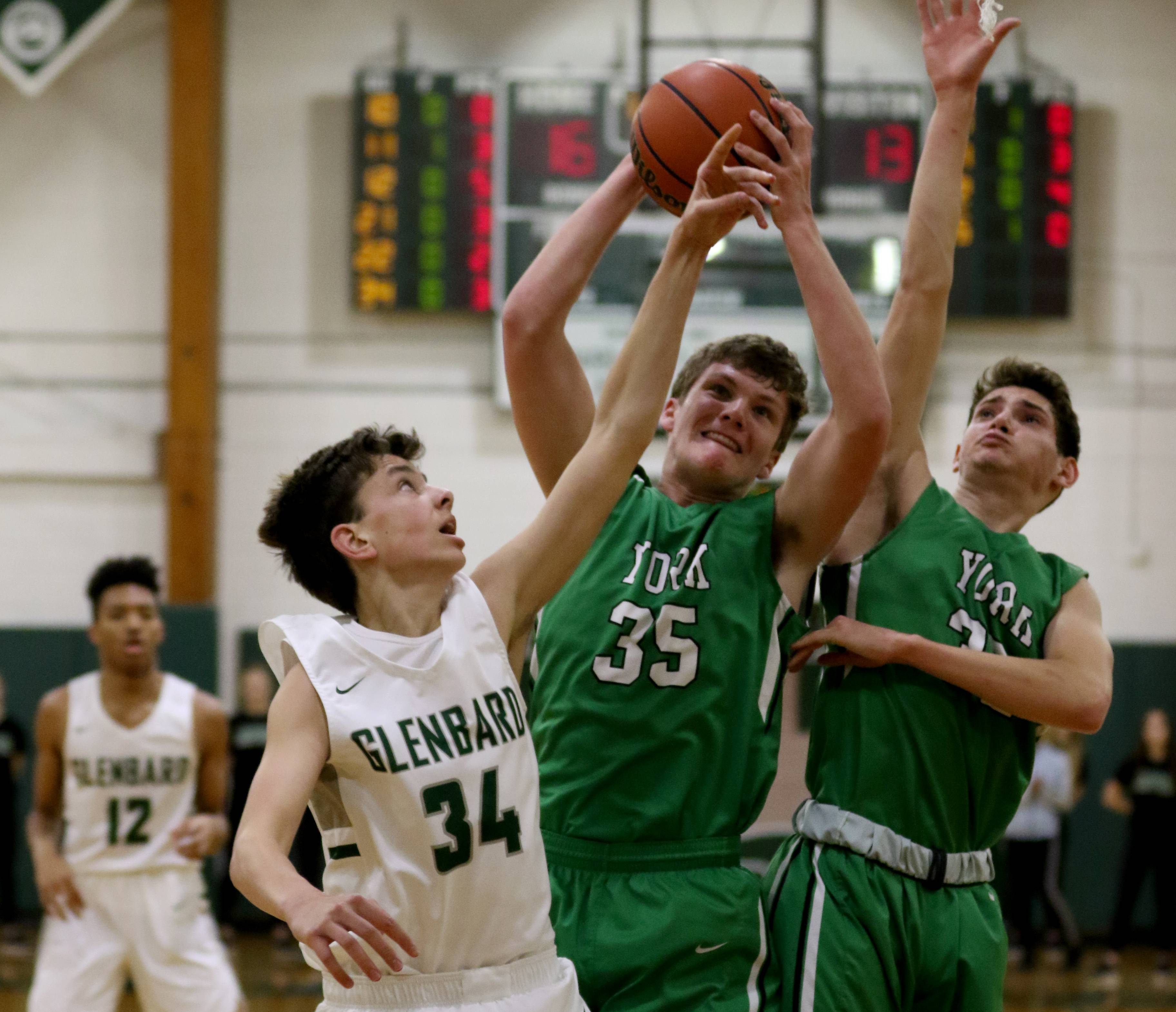 From left, Glenbard West's Braden Huff and York's Sam Walsh and Erik Cohn battle for a rebound during varsity boys basketball at Fred L. Biester Gymnasium on the campus of Glenbard West Tuesday night.