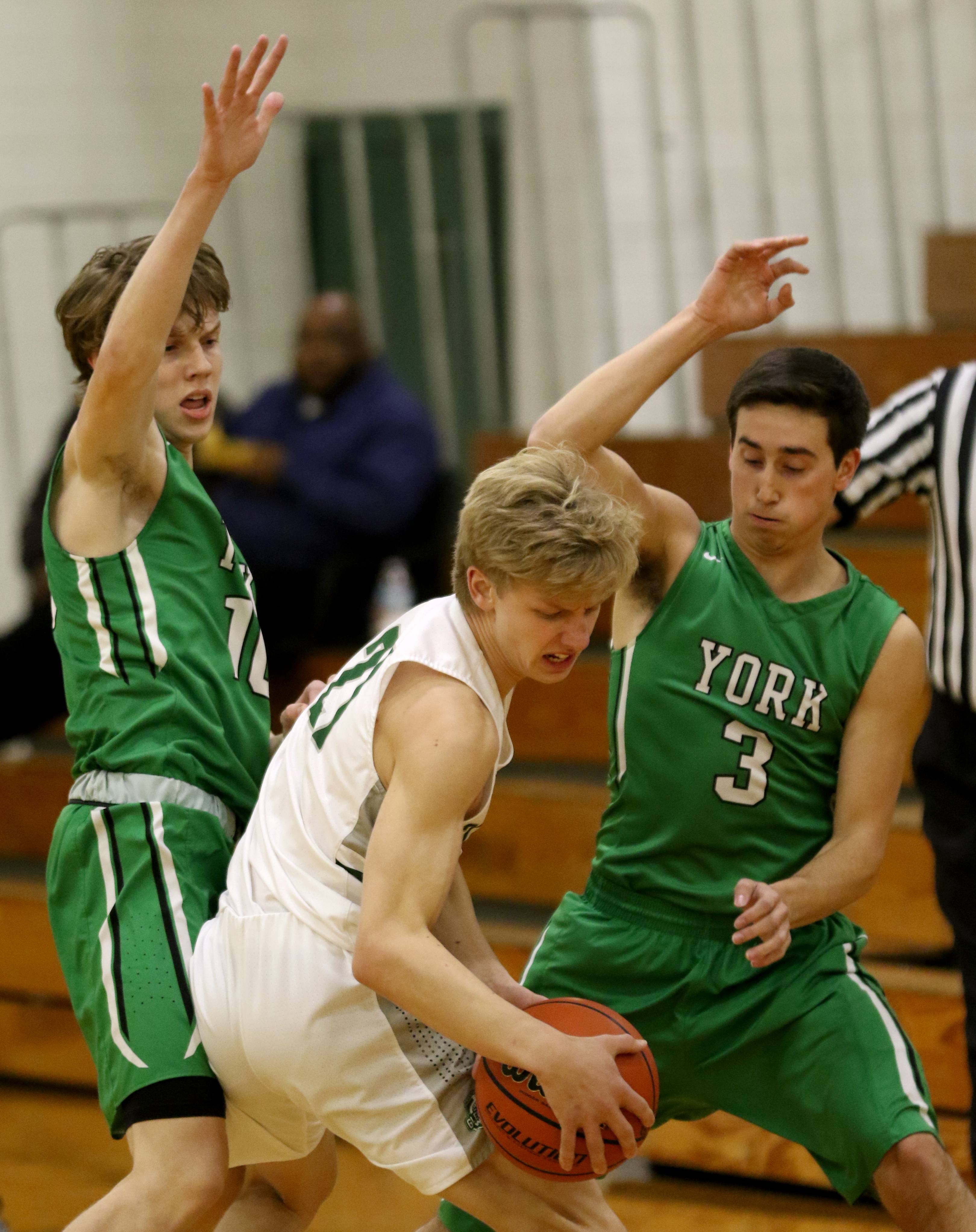 York's Nathan Shockey, left, and Nicholas Kosich, right, guard Glenbard West's Carter Lindstrom during varsity boys basketball at Fred L. Biester Gymnasium on the campus of Glenbard West Tuesday night.