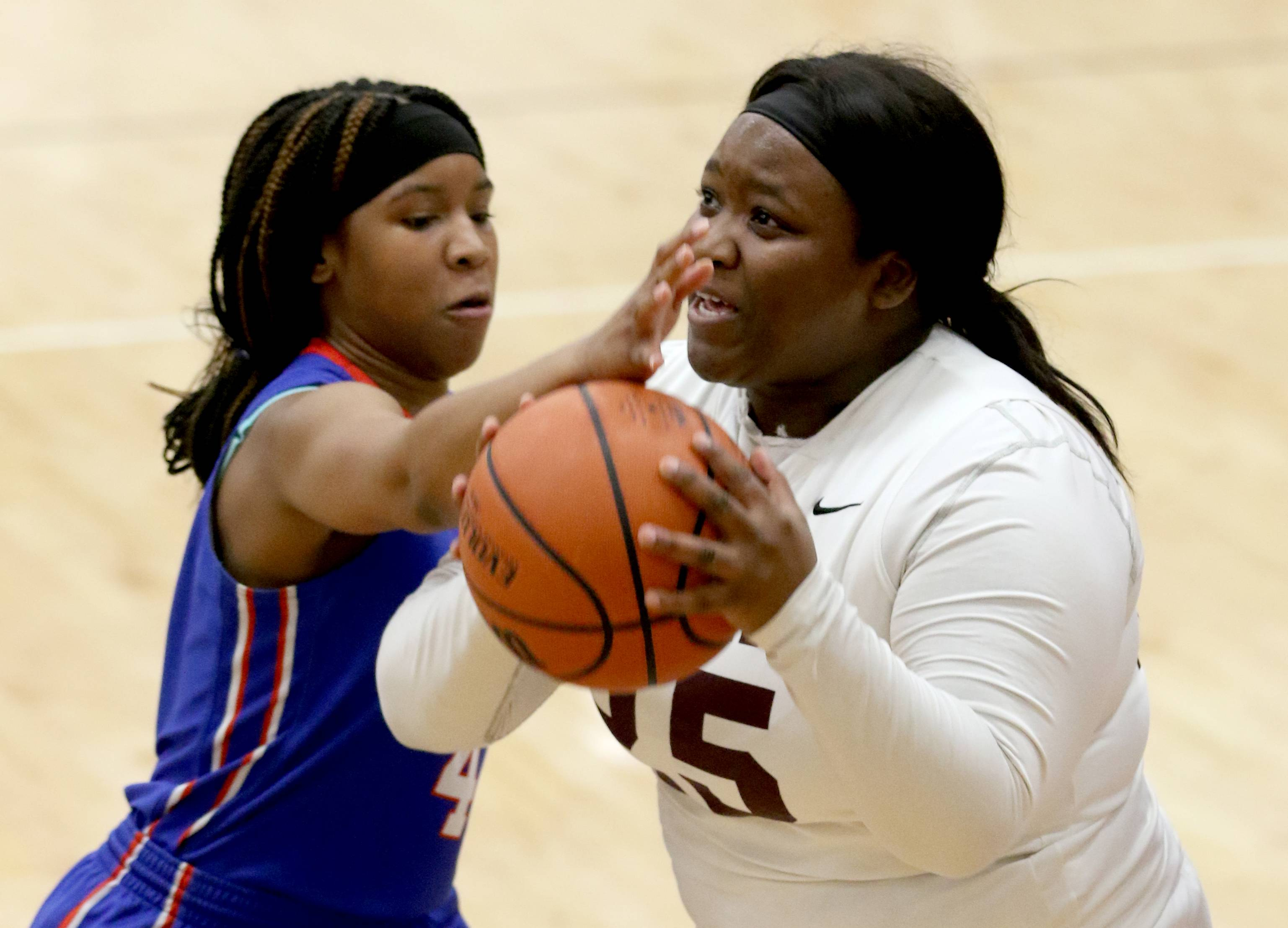 Larkin's  Keondra Baldwin, left, covers Elgin's Kamiya Harvey under the hoop during Elgin City Classic Girls Basketball Tournament action at Chesbrough Fieldhouse on the campus of Elgin High School Wednesday night.