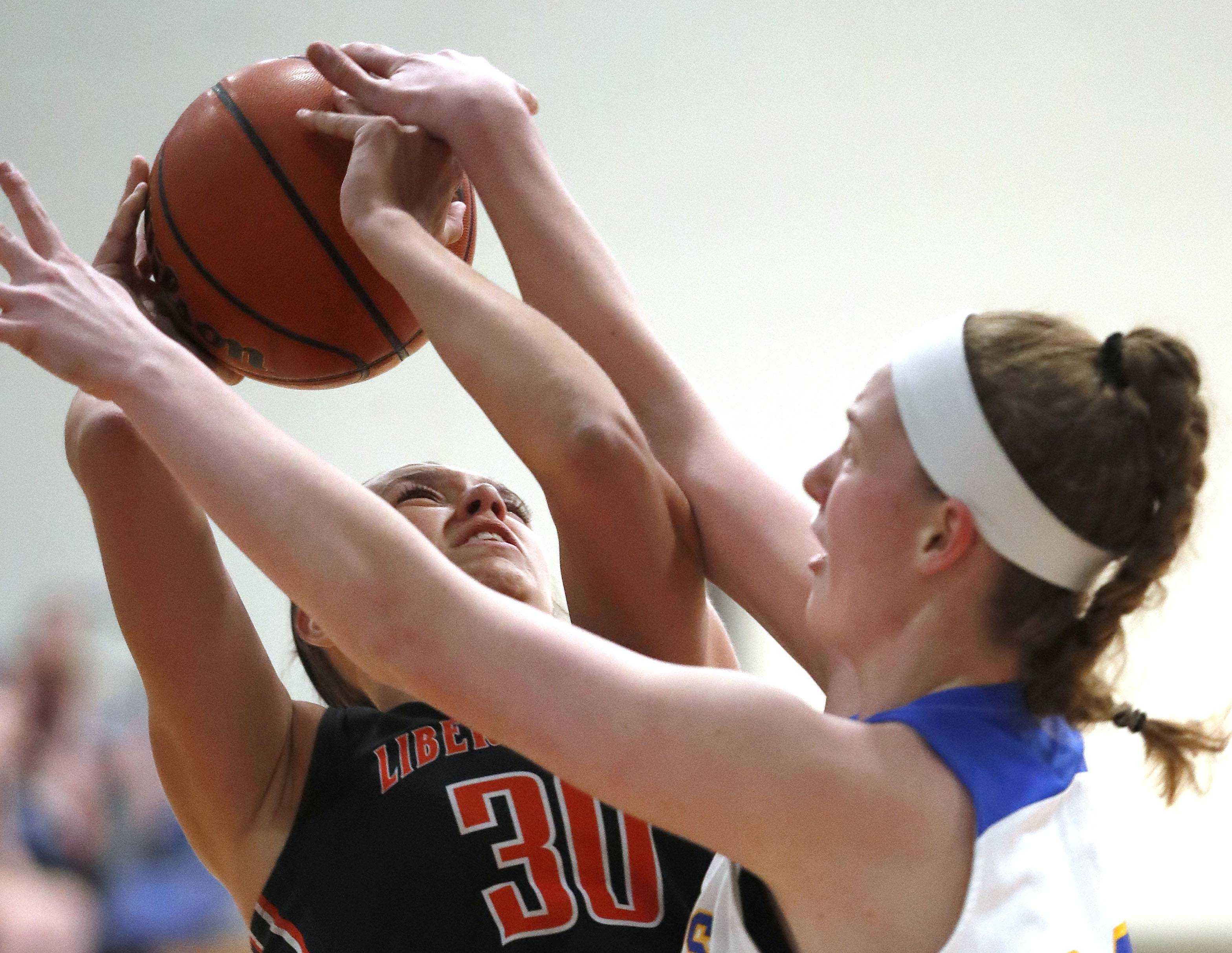 Libertyville's Maddie Spaulding, left, drive on Lake Forest's Ellie Pearson during their game Wednesday night in Lake Forest.