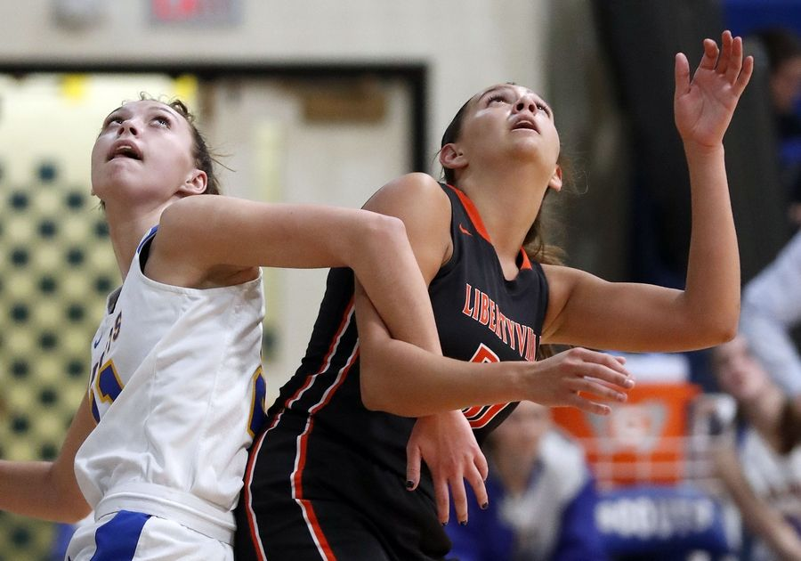 Lake Forest's Halle Douglass left, and Libertyville's Maddie Spaulding battle for position during their game Wednesday night in Lake Forest.
