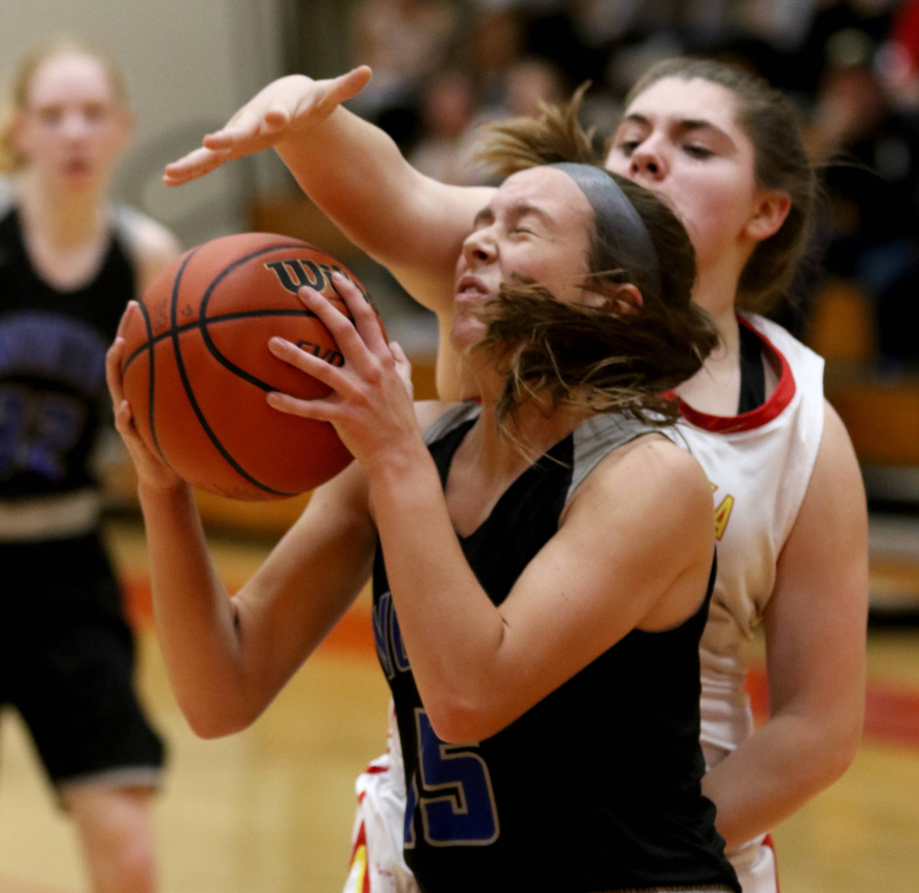 Batavia's Claire Nazos, back guards St. Charles North's Makenna Collins under the hoop during varsity girls basketball at Batavia Thursday night.