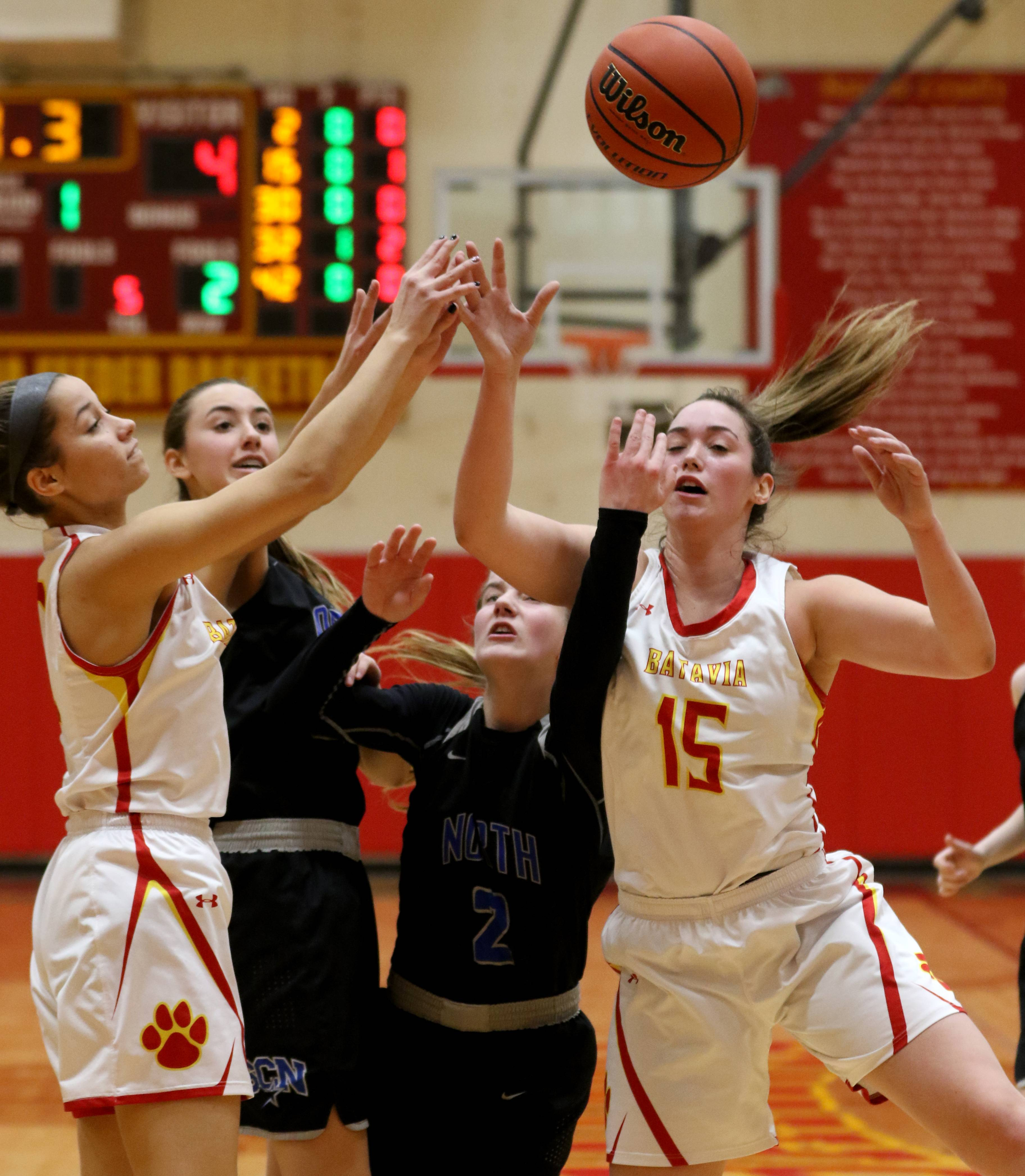 Batavia's Katherine Polick, left, and Ava Sergio, right, along with St. Charles North's Tatum Settelmyer and Emma Ludwig look for a rebound during varsity girls basketball at Batavia Thursday night.