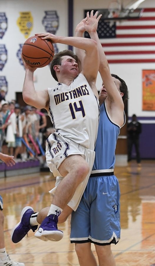 Prospect's Jon Kreidler blocks the path of Rolling Meadows' Sean Nolan in the boys basketball varsity matchup at Rolling Meadows on Friday.