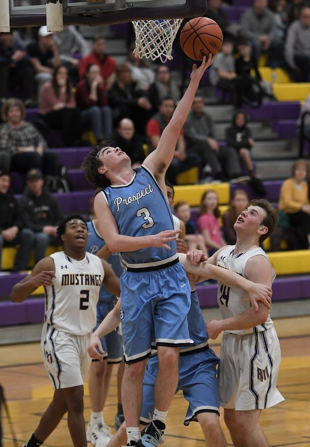 Prospect's TJ Johannesen tries for two despite pressure from the Rolling Meadows' defense in the boys basketball varsity matchup at Rolling Meadows on Friday.