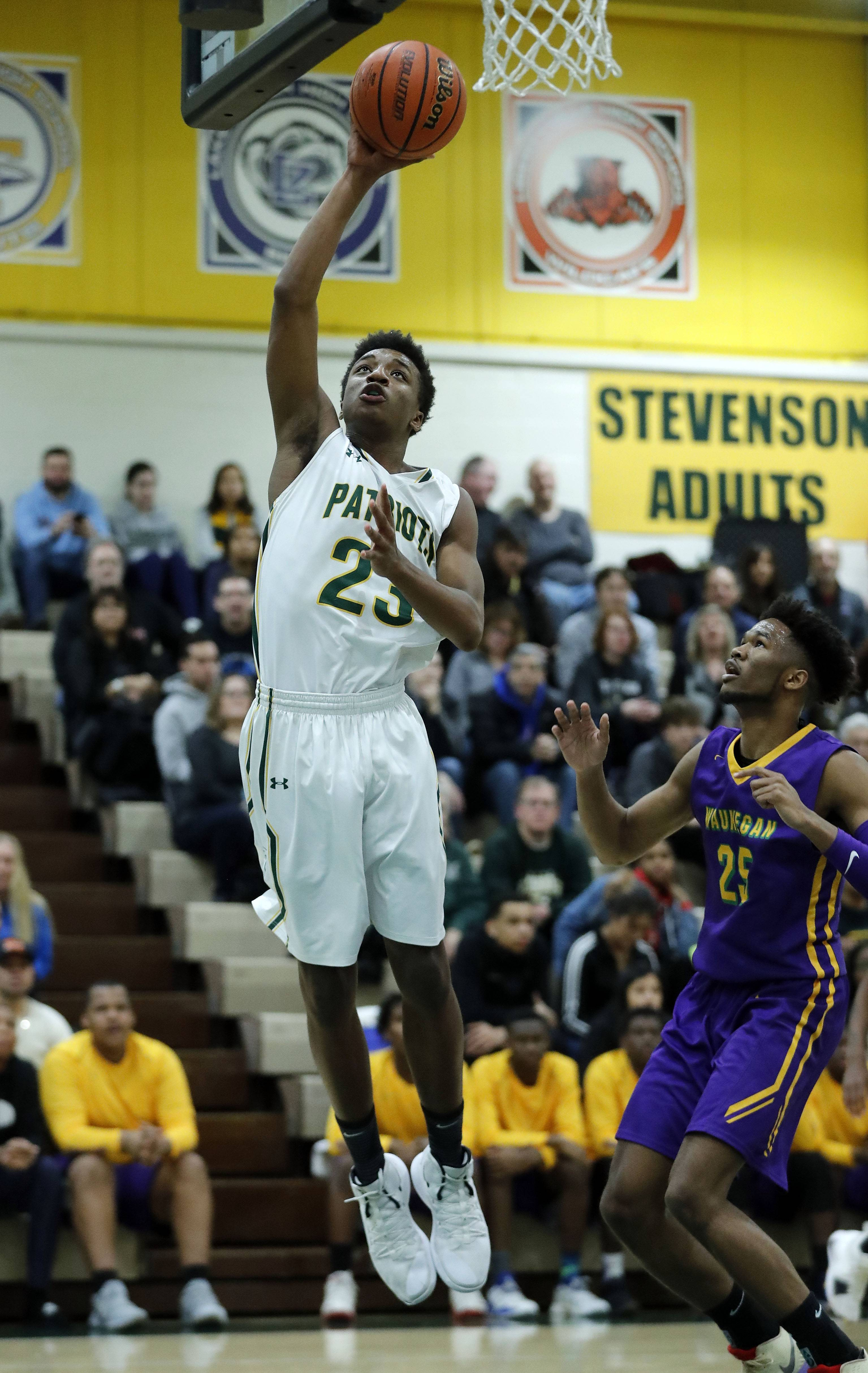 Stevenson's RJ Holmes drive in for a layup of Waukegan's Bryant Brown during their game Friday night in Lincolnshire.