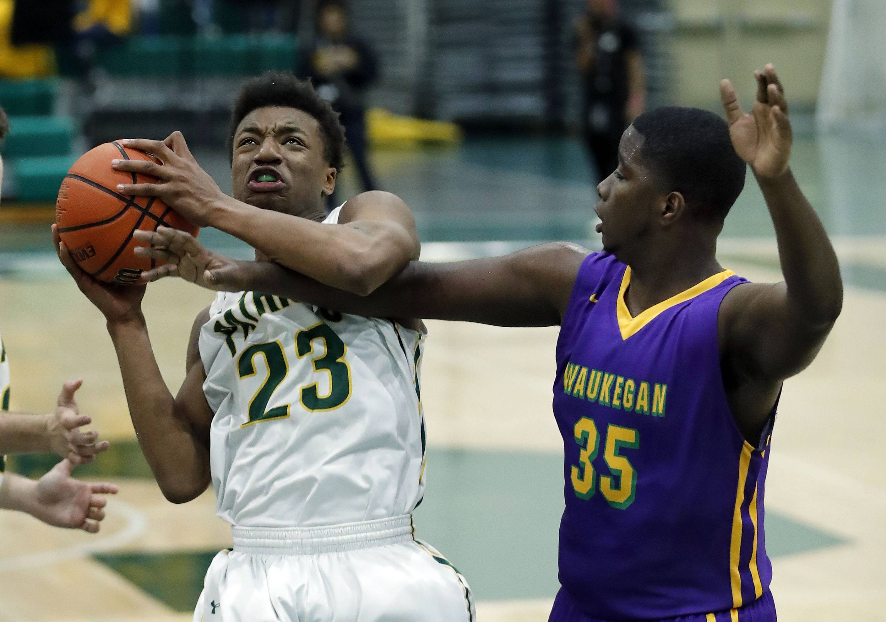 Stevenson's RJ Holmes (23) and Waukegan's Javeon Taylor battle for a rebound during their game Friday night in Lincolnshire.