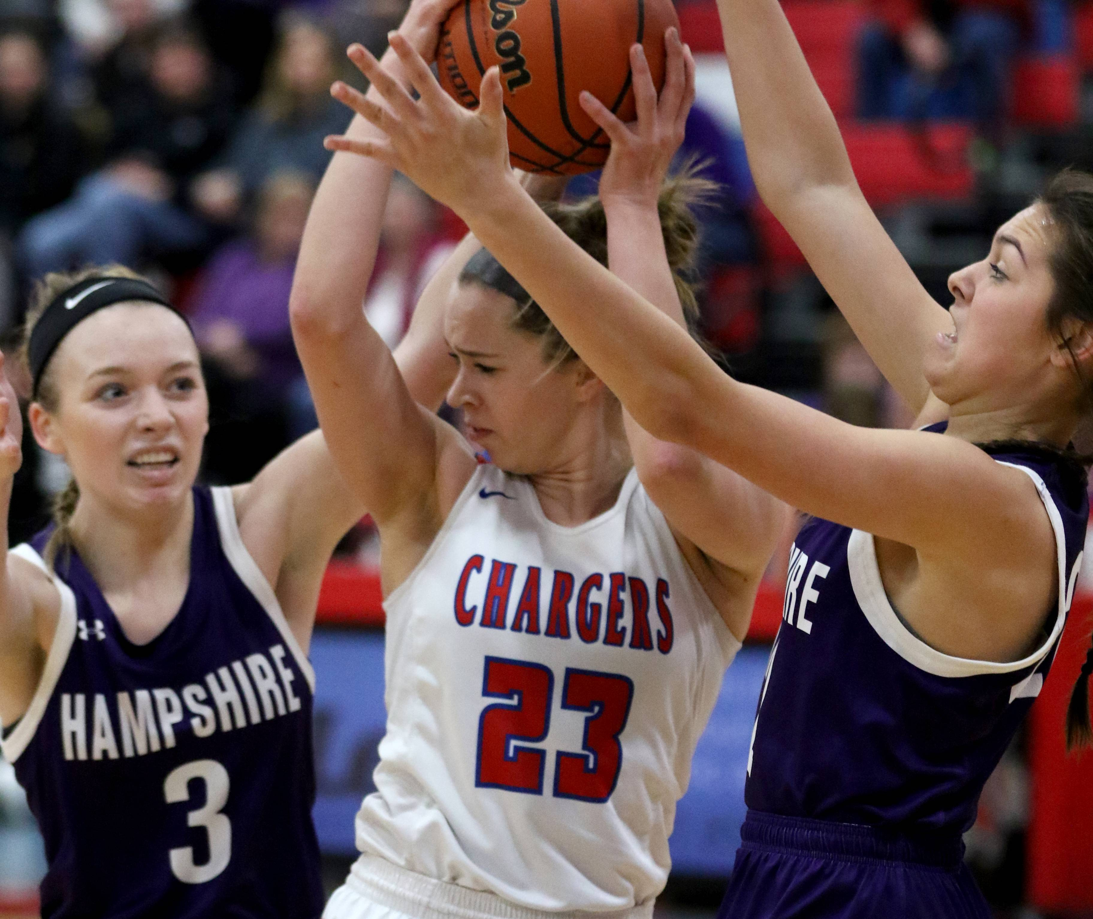 Hampshire's Ally Cermak, left, and Veronica Walker, right, swarm Dundee-Crown's Kendall Kieltyka during the Whip-Purs' win in Carpentersville Friday night.