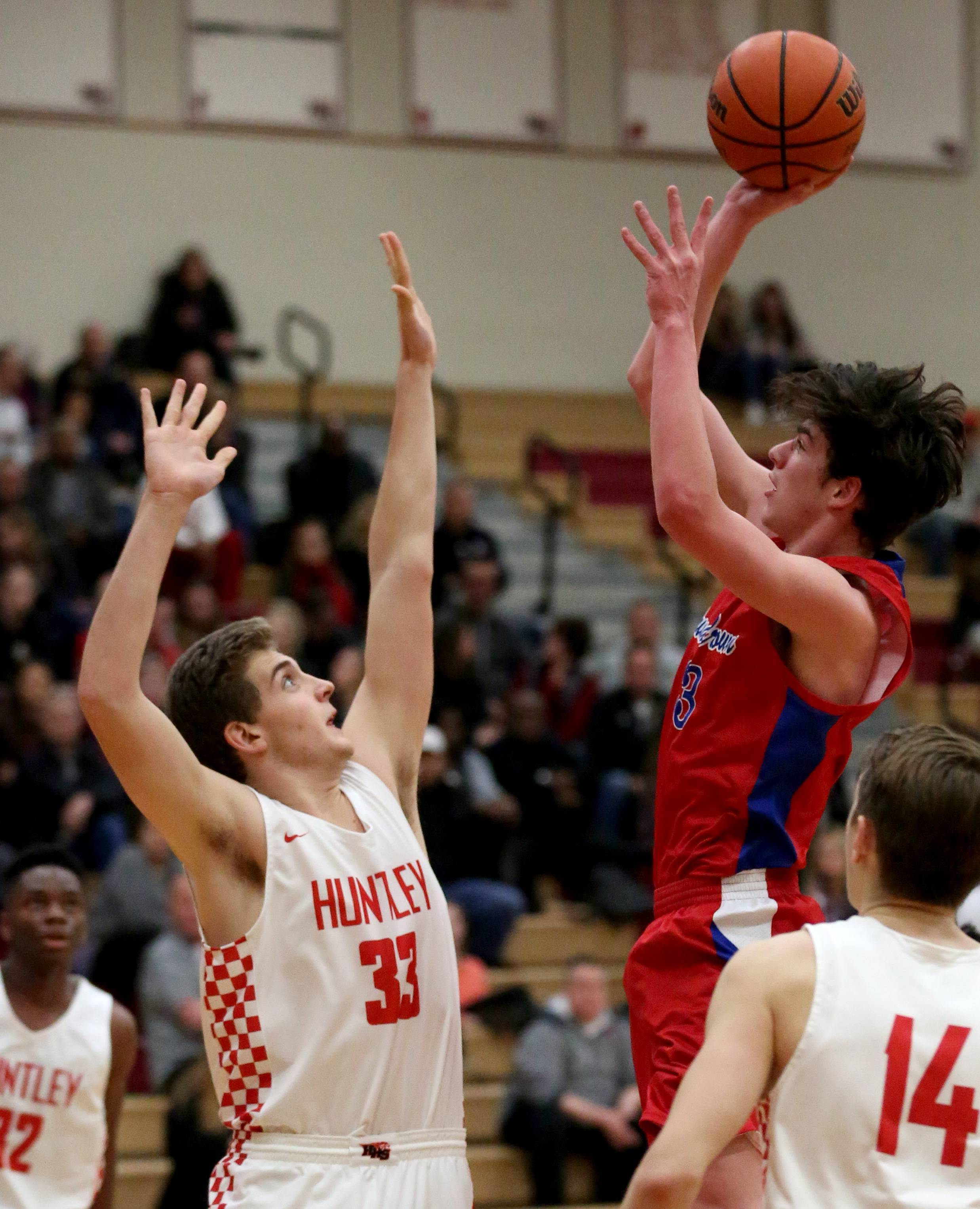 Dundee-Crown's Jack Michalski, right, rises for a shot as Huntley's Luke DiFrancesca defends during varsity basketball at Huntley Tuesday night.