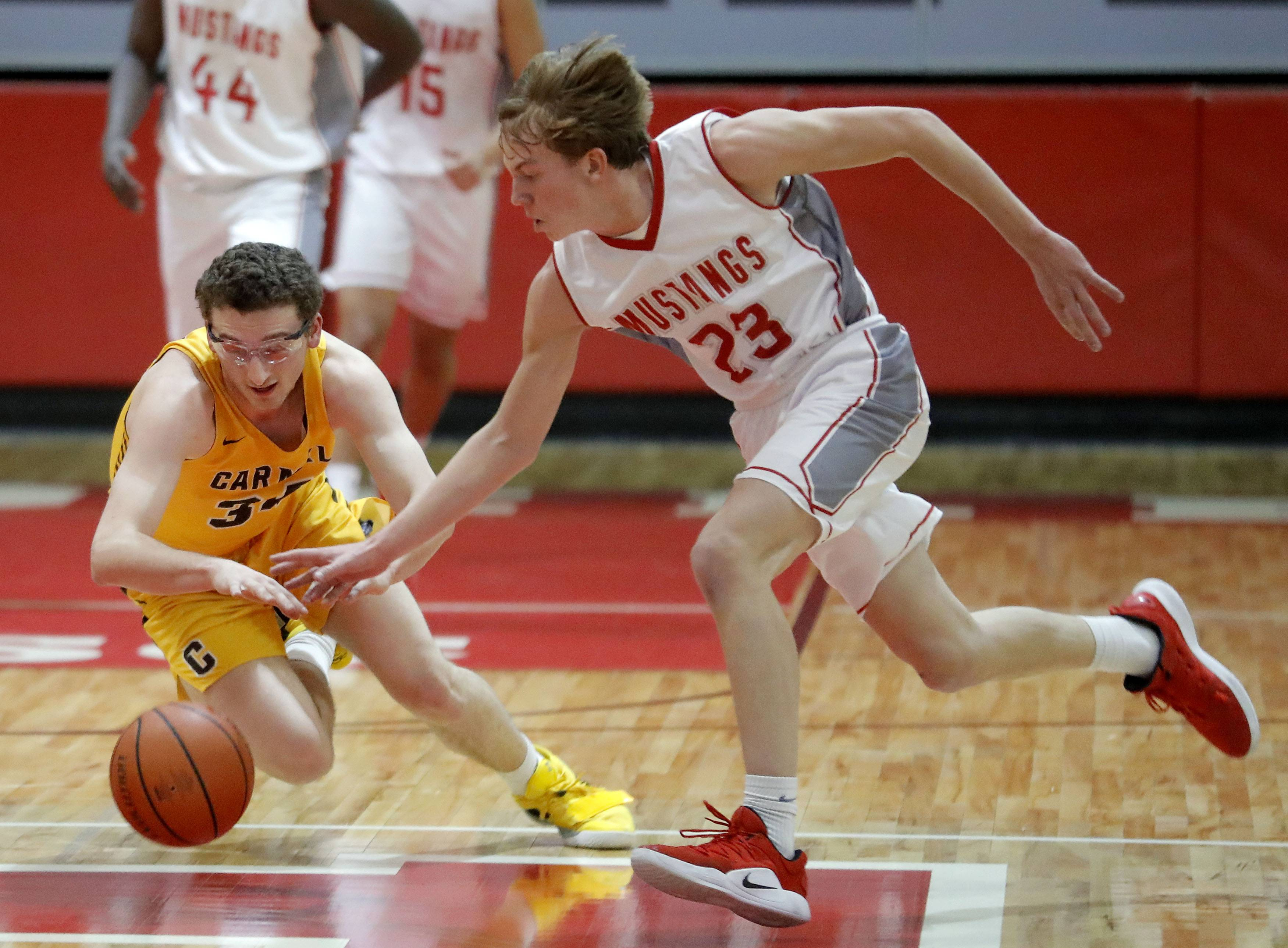 Carmel's Johnny Roeser left, and Mundelein's Jack Bikus battle for a loose ball during their game Wednesday at Mundelein High School.