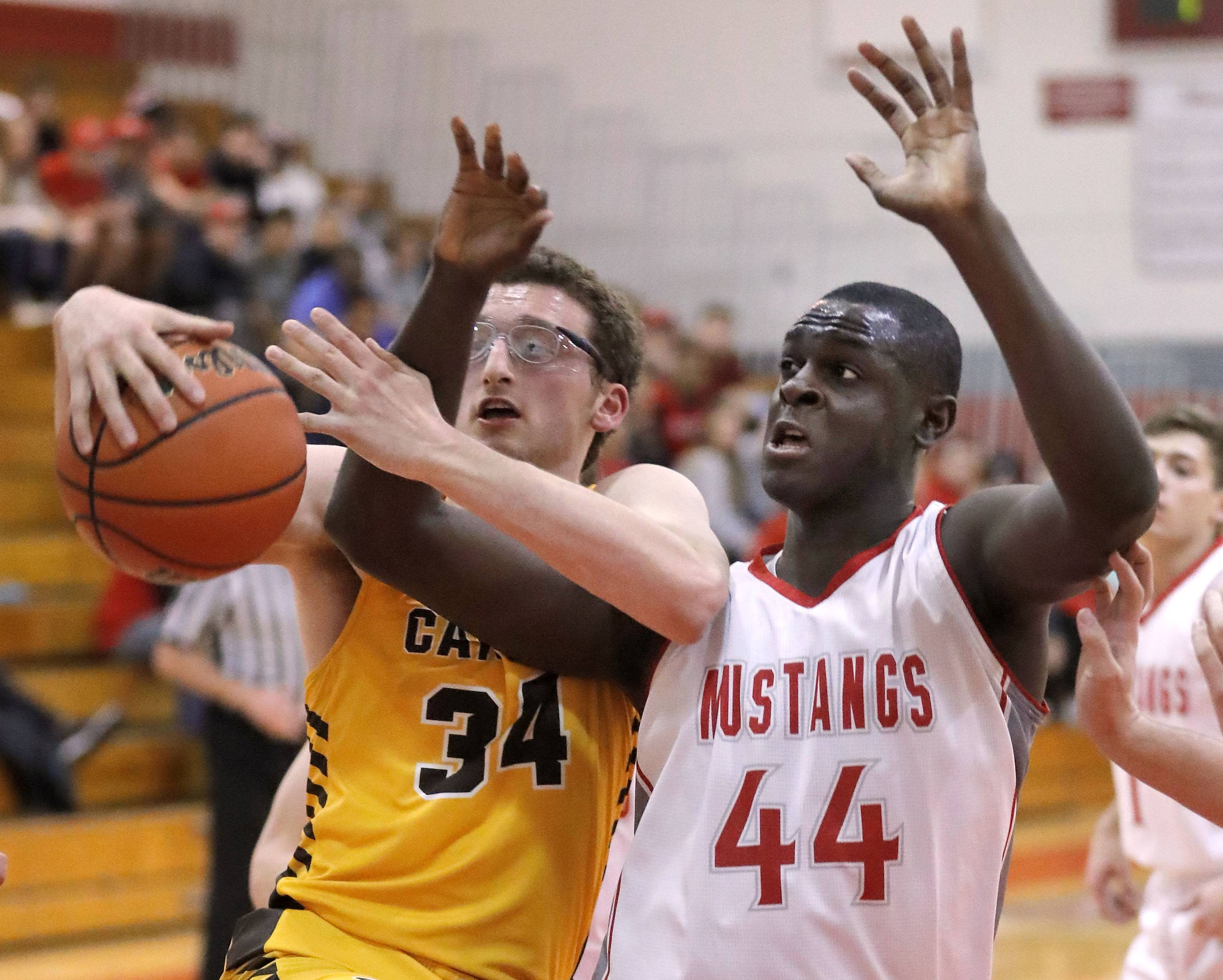 Carmel's Johnny Roeser, left, and Mundelein's Scottie Ebube battle for a rebound during their game Wednesday at Mundelein High School.