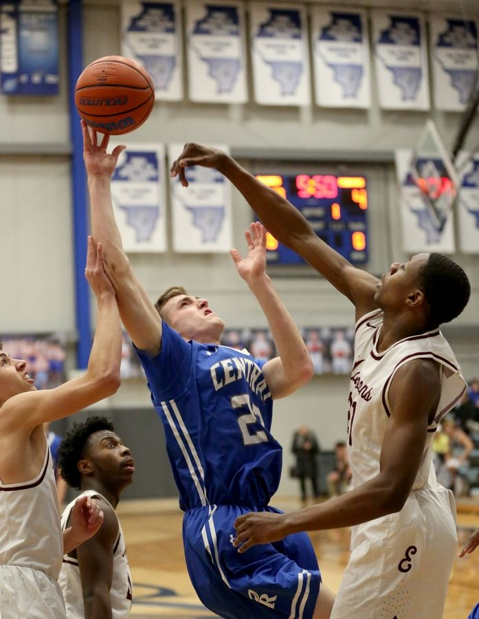Burlington Central's Jake Lenschow, center, shoots under pressure from Elgin's Trey Yarber, left, and Jeffrey Lomax, right, during MLK Classic varsity boys basketball tournament action Wednesday evening.