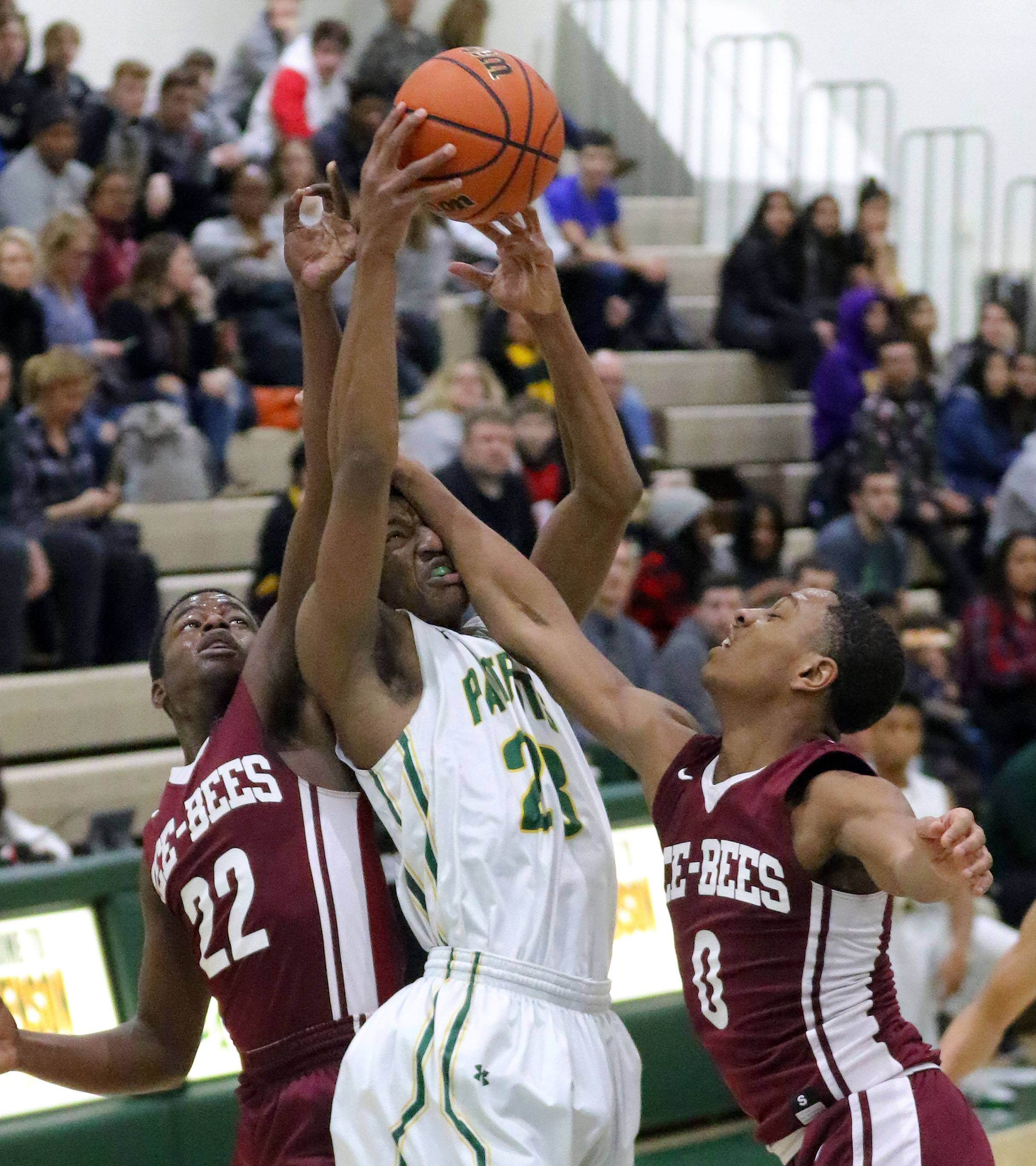 Stevenson's RJ Holmes, middle, battles for a rebound with Zion-Benton's Floyd Bailey (22) and Quentin Williams during their game Friday in Lincolnshire.