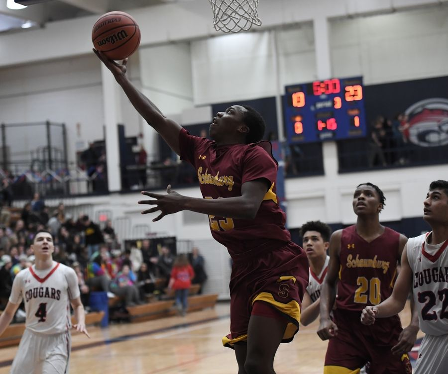 Schaumburg's Heze Trotter delivers 2 points and reaches the 1,000 point mark for his career against Conant in the boys varsity basketball game at Conant on Friday.