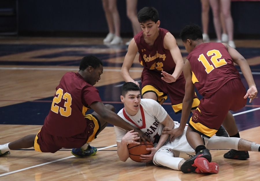Conant's Jonathan Kolev takes possession of a loose ball as Schaumburg's Heze Trotter, Vaurice Patterson and Arnav Karnik makes sure he stays on the floor in the boys varsity basketball game at Conant on Friday.