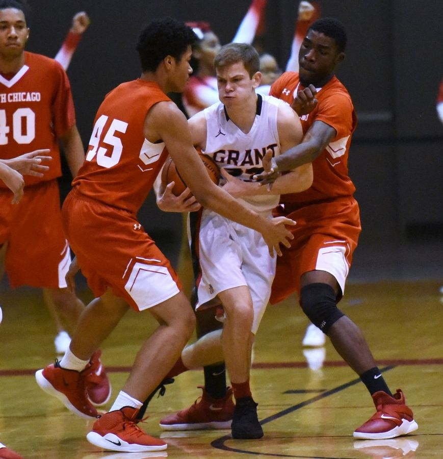 Grant's Henry Kusiak, center, is pressured by North Chicago's Raekwon McDuffy (45) and Achan Clinton during Friday's boys basketball game in Fox Lake.