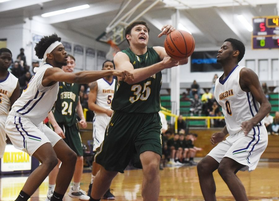 Stevenson's Matthew Kaznikov has the ball knocked free from his grasp while driving to the basket against Waukegan's Bryant Brown, left, and Jaylin Cunningham during Tuesday's game in Waukegan.