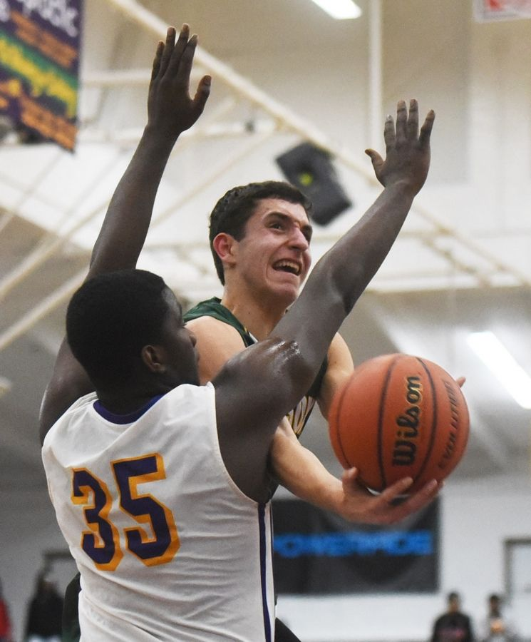 Stevenson's John Ittounas drives to the basket against Waukegan's Kavon Colder during Tuesday's game in Waukegan.
