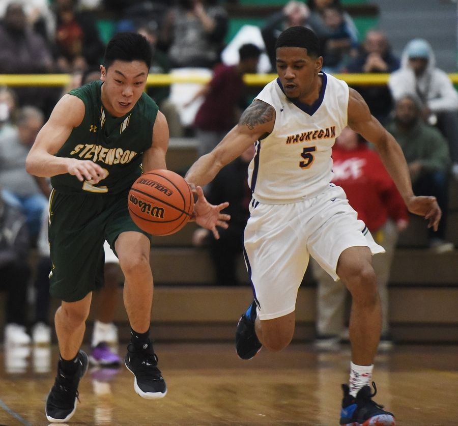 Waukegan's Jordan Brown, right, steals the ball from Stevenson's Luke Chieng during Tuesday's game in Waukegan.