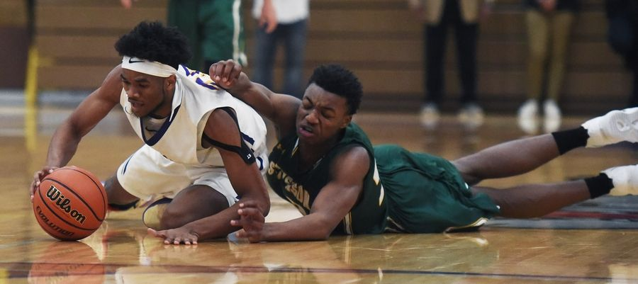 Waukegan's Bryant Brown, left, and Stevenson's Robert Holmes dive to the floor for a loose ball during Tuesday's game in Waukegan.