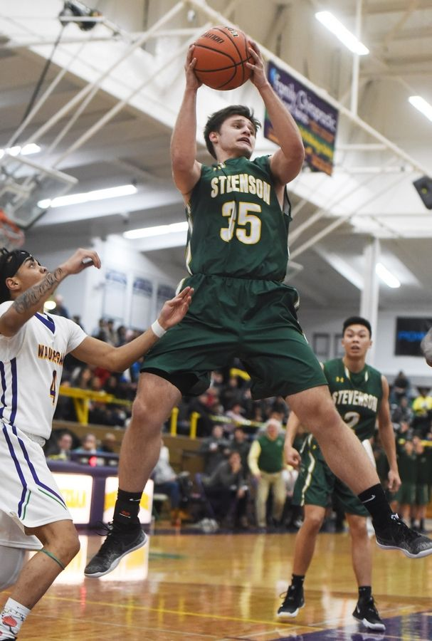 Stevenson's Matthew Kaznikov grabs a rebound in front of Waukegan's Andre White Jr. during Tuesday's game in Waukegan.