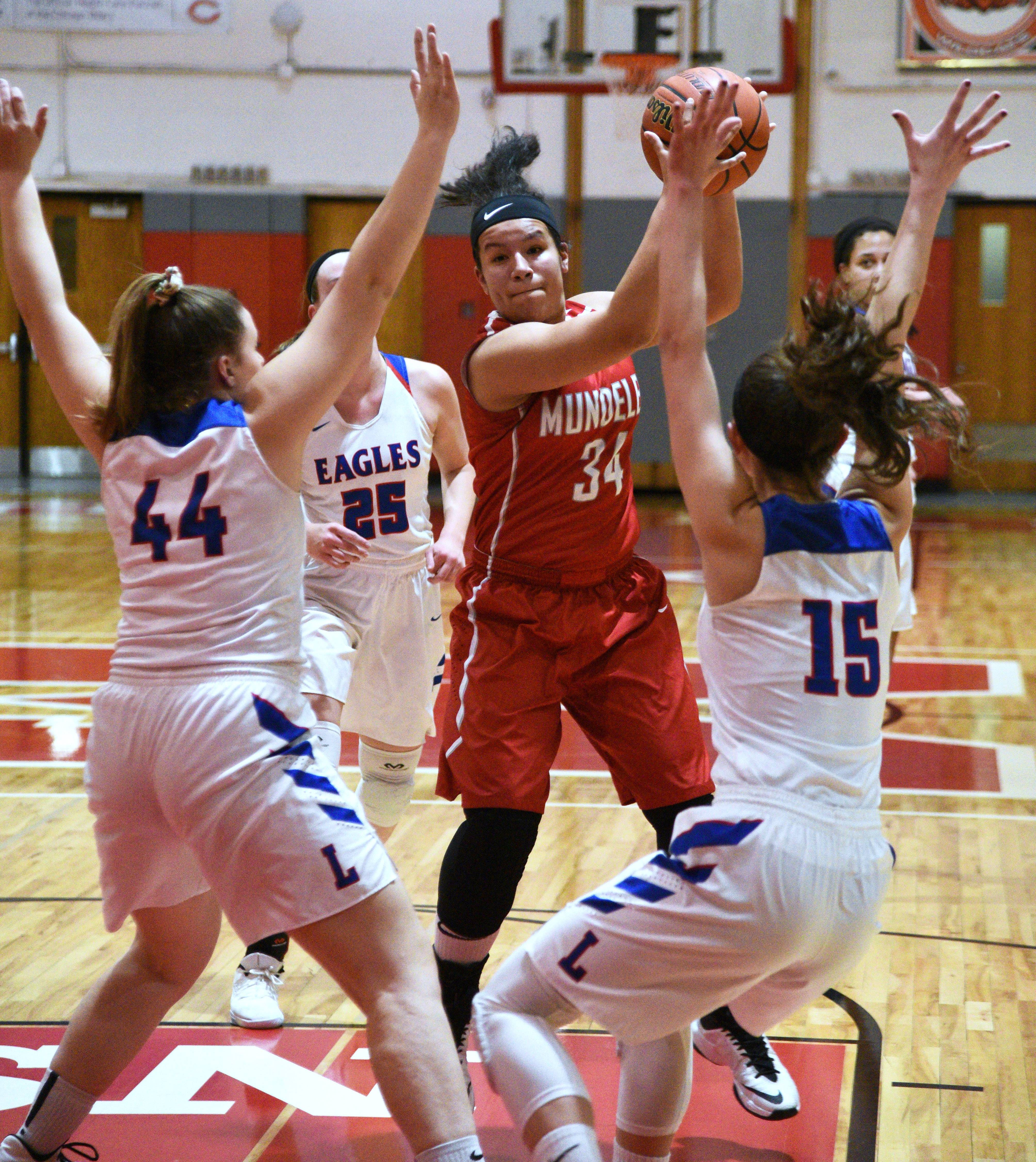 Mundelein's Kendall Klatt (34) is pressured by a host of Lakes players during Monday's girls regional basketball game in Mundelein.