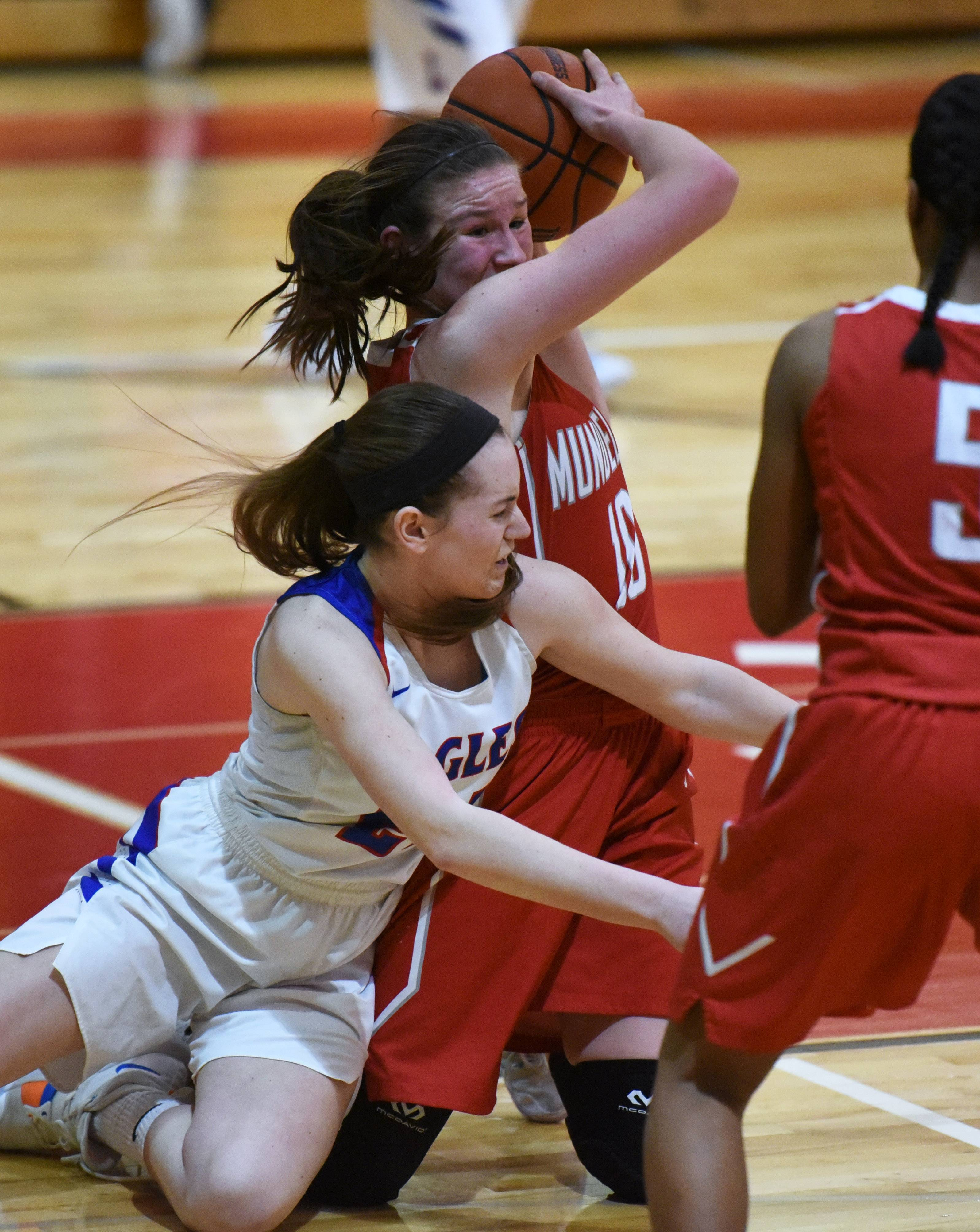 Mundelein's Morgan Frank keeps the ball away from Lakes' Taylor Lehman during Monday's girls regional basketball game in Mundelein.