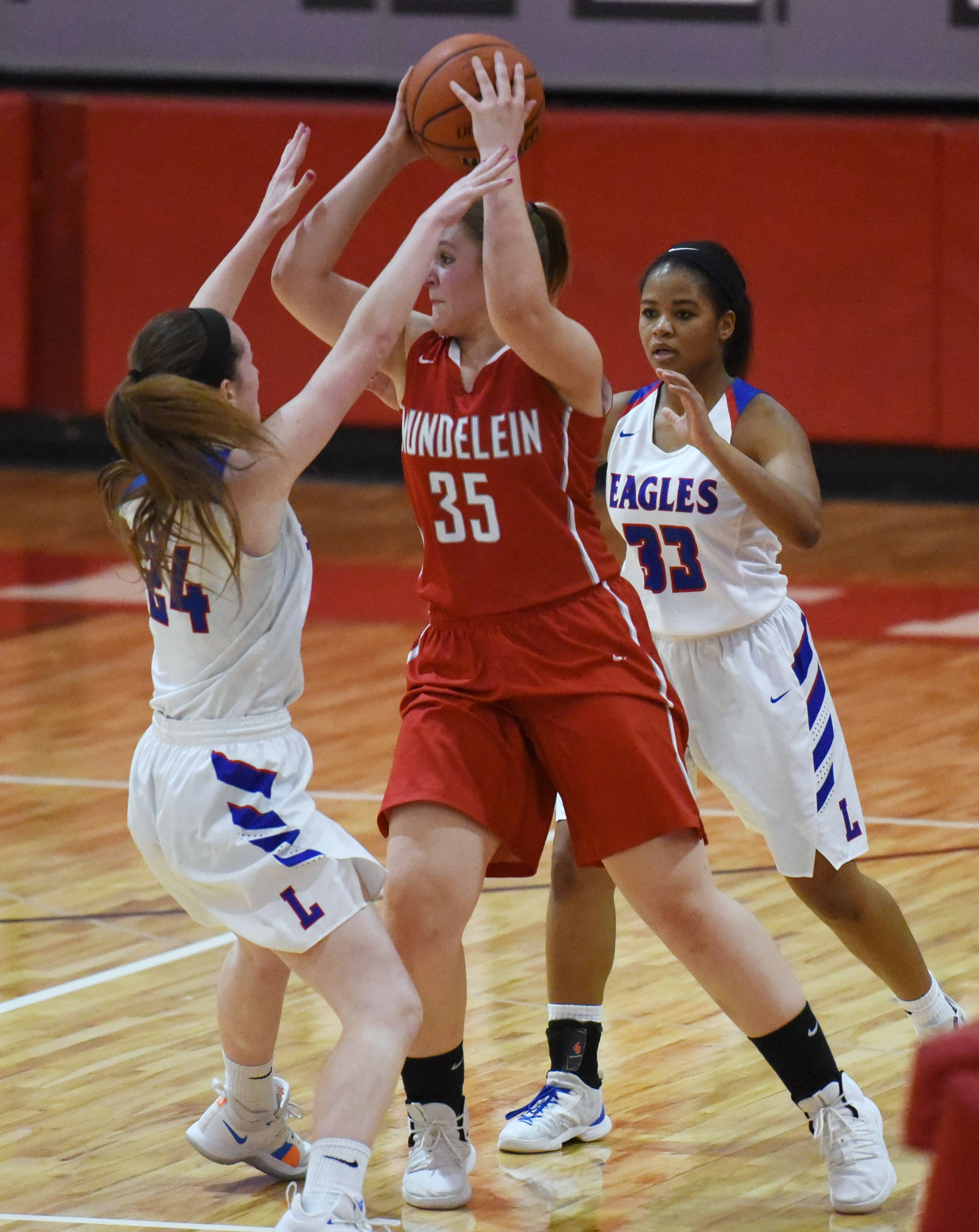Mundelein's Gerda Boreika (35) is pressured by Lakes' Taylor Lehman (24) and Brittany Washington during Monday's girls regional basketball game in Mundelein.