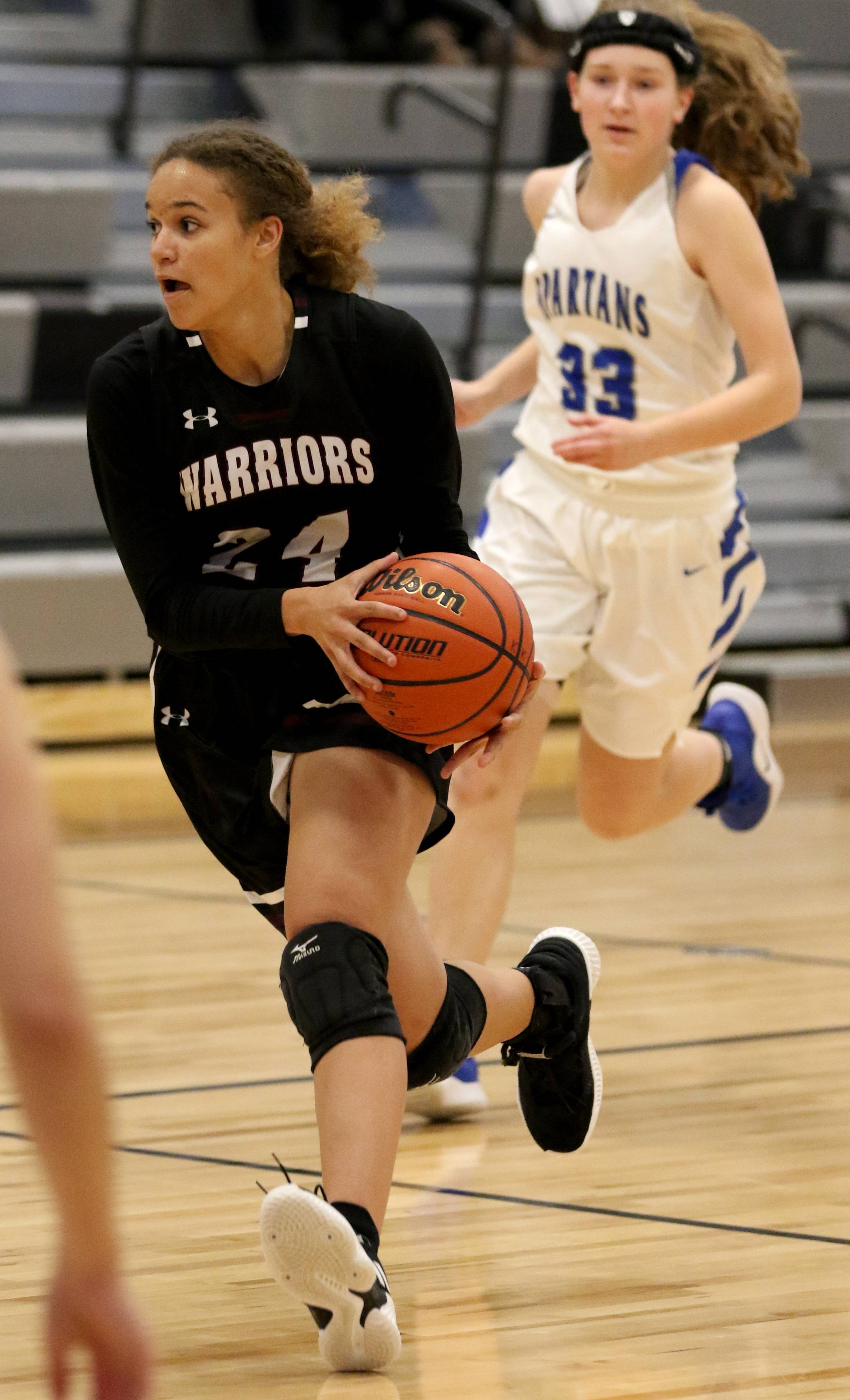 Wheaton Academy's Imani Hillmer moves with the ball against St. Francis during regional girls varsity basketball at Kaneland High School Monday night.