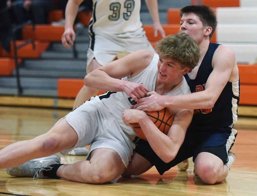 Libertyville's Will Moore, left, controls a loose ball in front of Buffalo Grove's Tyler Kipley during Wednesday's game in Libertyville.