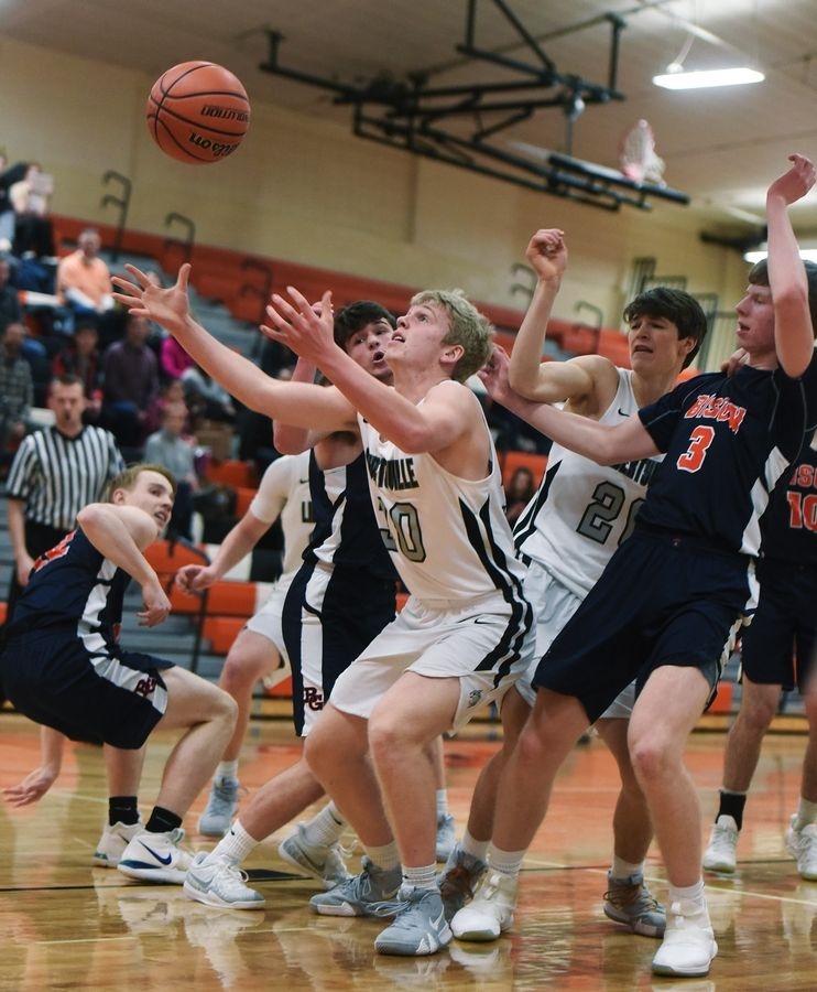 Libertyville's Blake Ellingson takes control of a loose ball in front of the Buffalo Grove defense including Nathan Cole, right, during Wednesday's game in Libertyville.