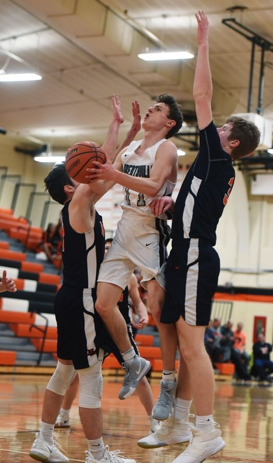Libertyville's Josh Steinhaus drives to the basket between Buffalo Grove's Michael Nowakowski, left, and Nathan Cole during Wednesday's game in Libertyville.