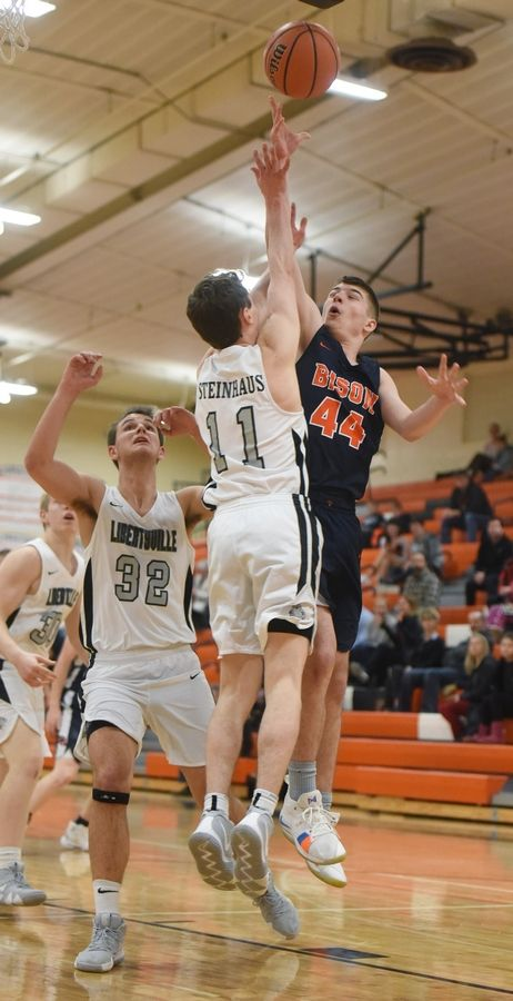 Buffalo Grove's Sloan Kipley, right, shoots against Libertyville defenders Travis Clark, left, and Josh Steinhaus during Wednesday's game in Libertyville.