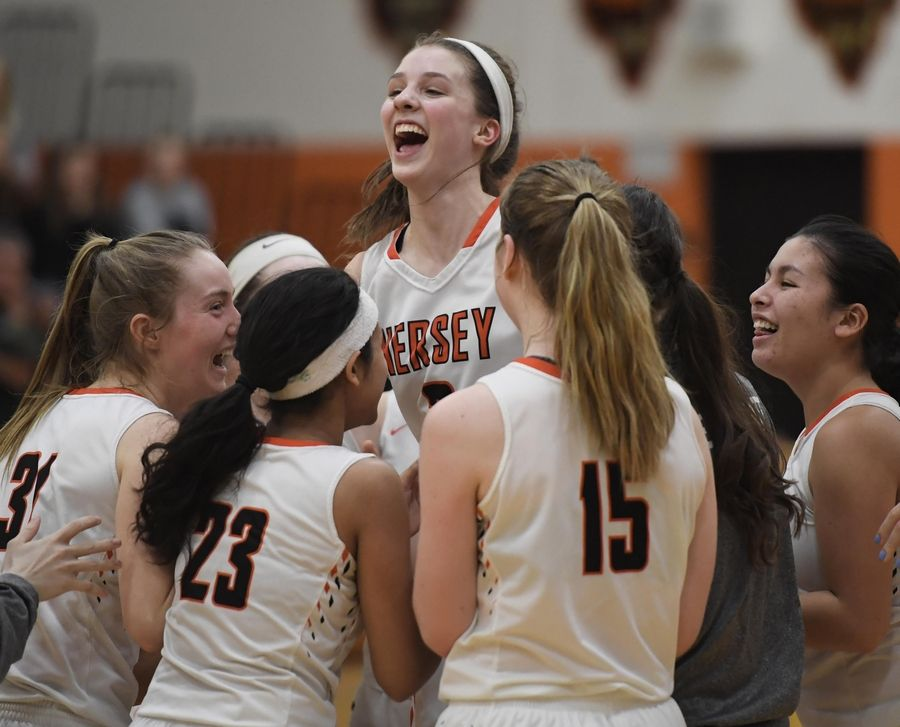 Hersey's Mary McGrath jumps with her teammates as they celebrate their win against Stevenson in the Hersey girls basketball regional championship game Thursday in Arlington Heights.