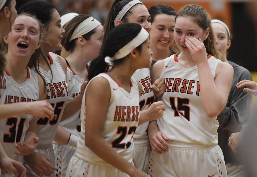Hersey's Emily Collins wipes tears as she gathers with teammates to receive the trophy after defeating Stevenson in the Hersey girls basketball regional championship game Thursday in Arlington Heights.