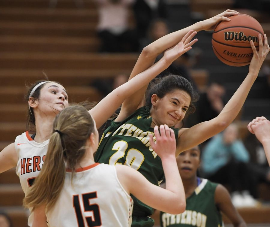 Stevenson's Avery King pulls a rebound away from Hersey's Maddie Jacobson in the Hersey girls basketball regional championship game Thursday in Arlington Heights.