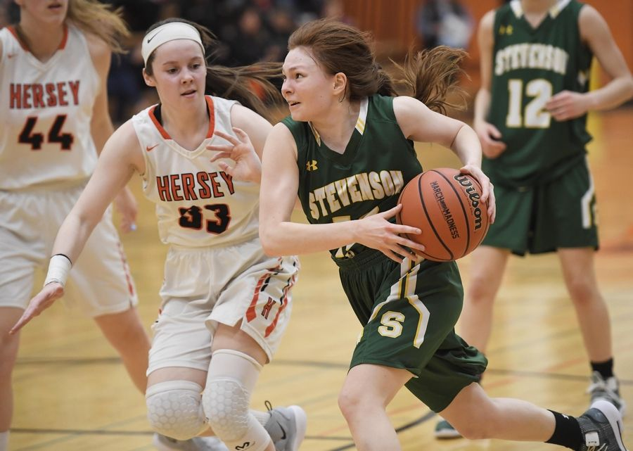 Stevenson's Nicole Ware charges for the basket against Hersey's Mary Kate Fahey in the Hersey girls basketball regional championship game Thursday in Arlington Heights.
