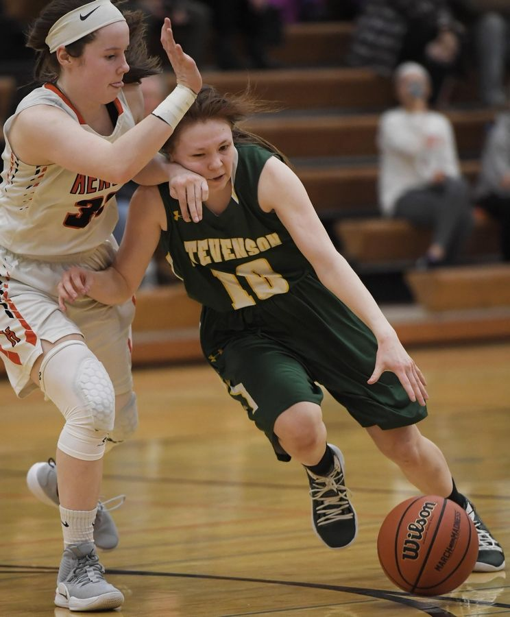 Stevenson's Nicole Ware runs into the defense of Hersey's Mary Kate Fahey in the Hersey girls basketball regional championship game Thursday in Arlington Heights.