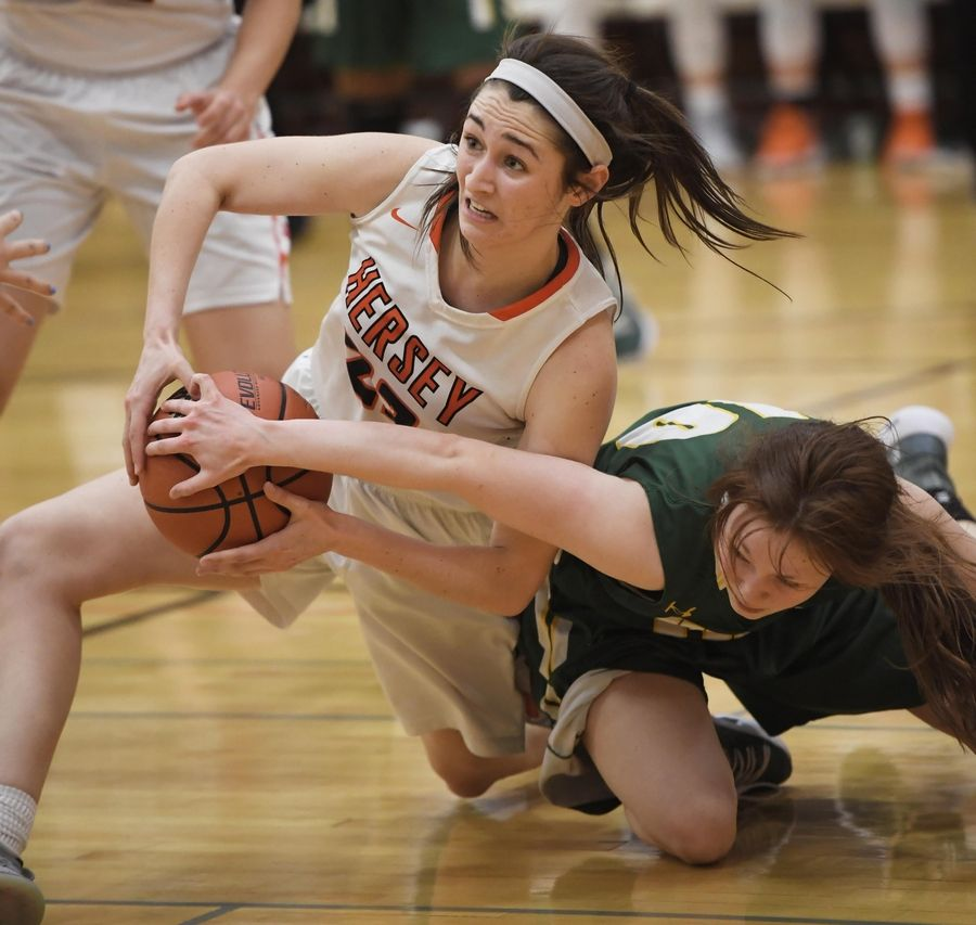 Hersey's Maddie Jacobson tries to get the ball to a teammate as Stevenson's Nicole Ware battles her in the Hersey girls basketball regional championship game Thursday in Arlington Heights.