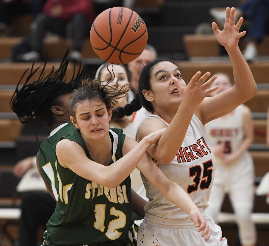 Hersey's Aya El-Fiky and Stevenson's Krissy Hill battle for the ball in the Hersey girls basketball regional championship game Thursday in Arlington Heights.