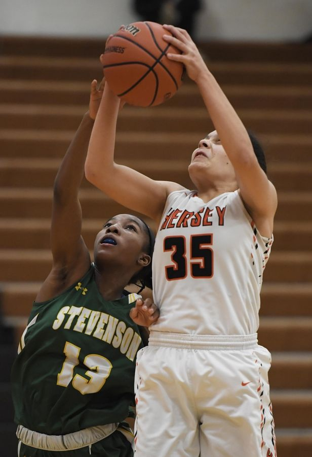 Hersey's Aya El-Fiky gets a rebound over Stevenson's Simone Sawyer in the Hersey girls basketball regional championship game Thursday in Arlington Heights.